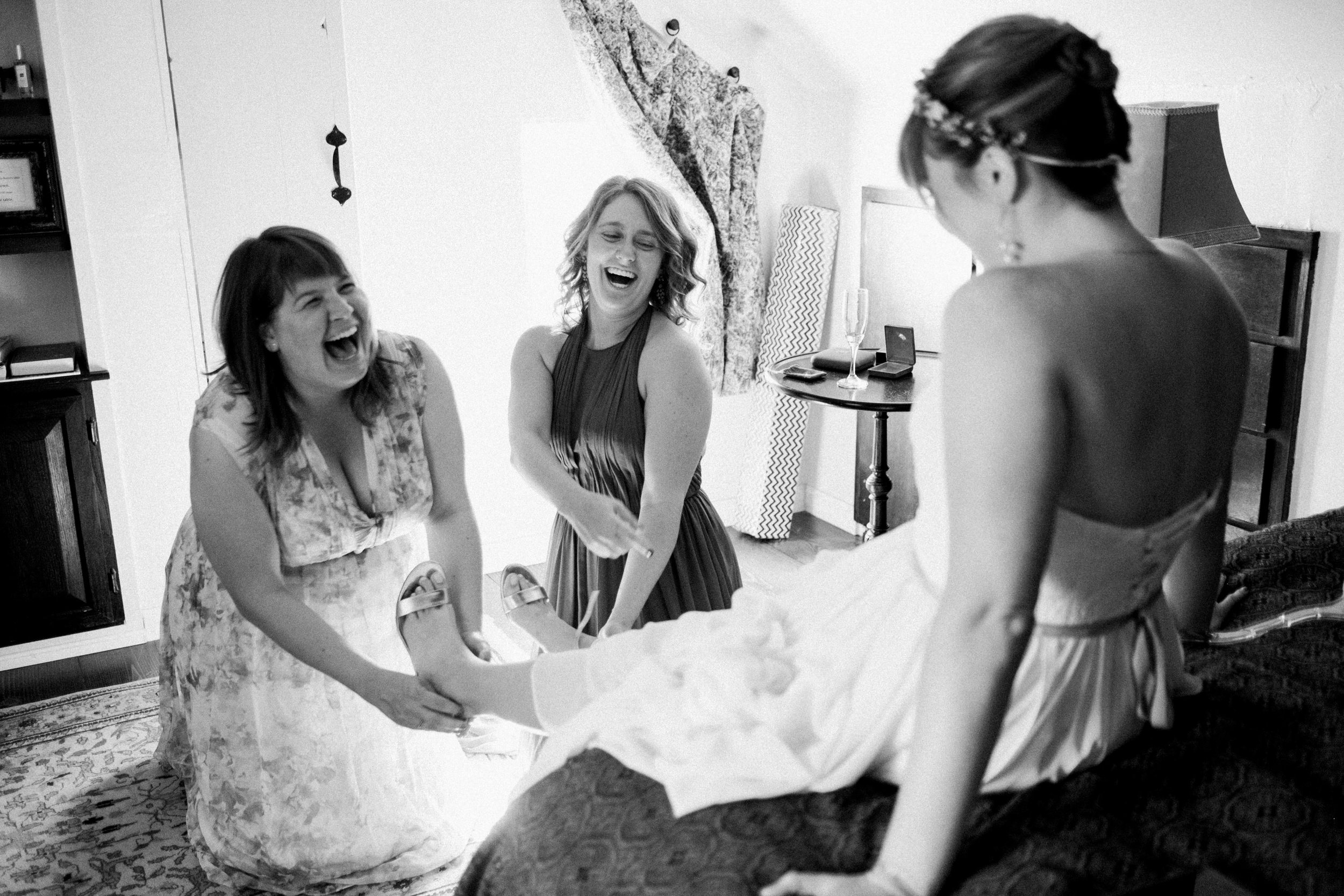Bride and bridesmaids getting ready putting shoes on