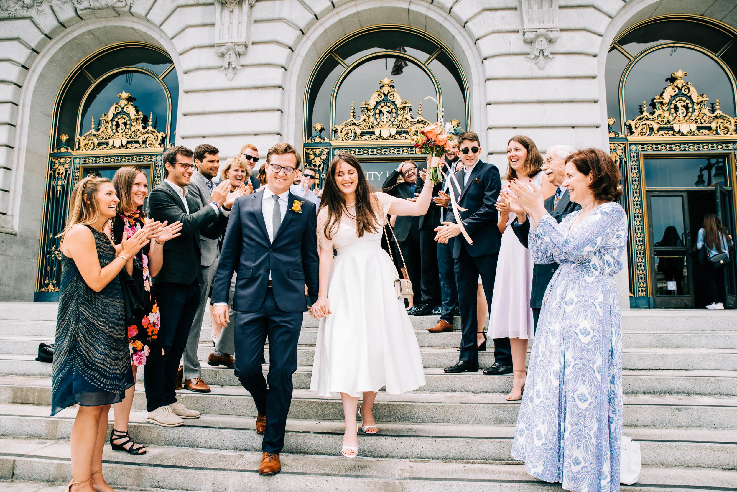 Bride and groom exit San Francisco City Hall wedding