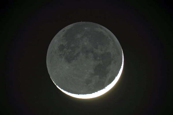 Earthshine is the bluish light from the Earth reflecting off the crescent Moon.