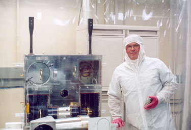 Earthshine President Randy Attwood poses with the MOST spacecraft in a clean room at UTIAS in Toronto in 2002