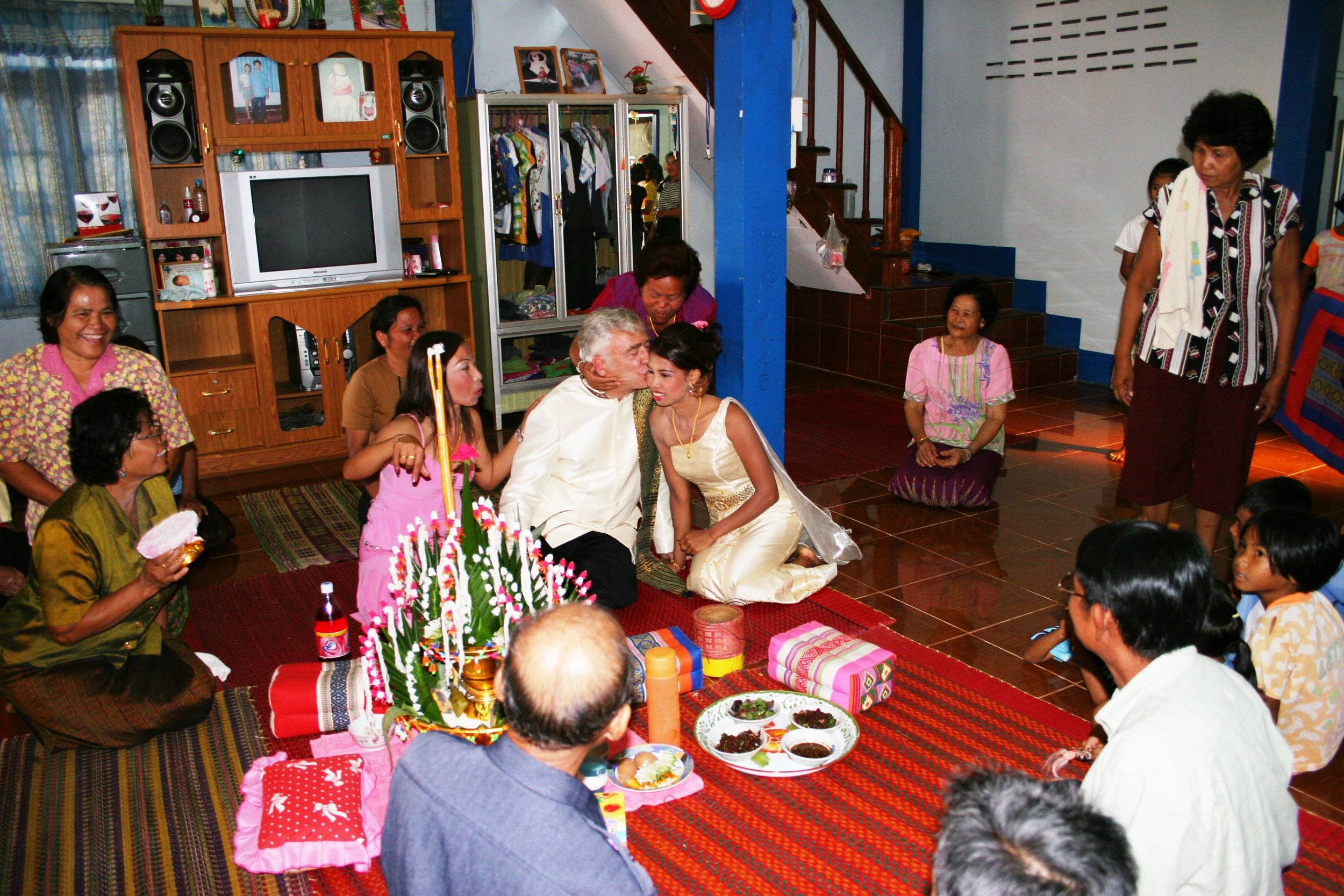 The groom kisses the bride of course.  This may be another western custom as kissing in public is frowned upon in Thailand