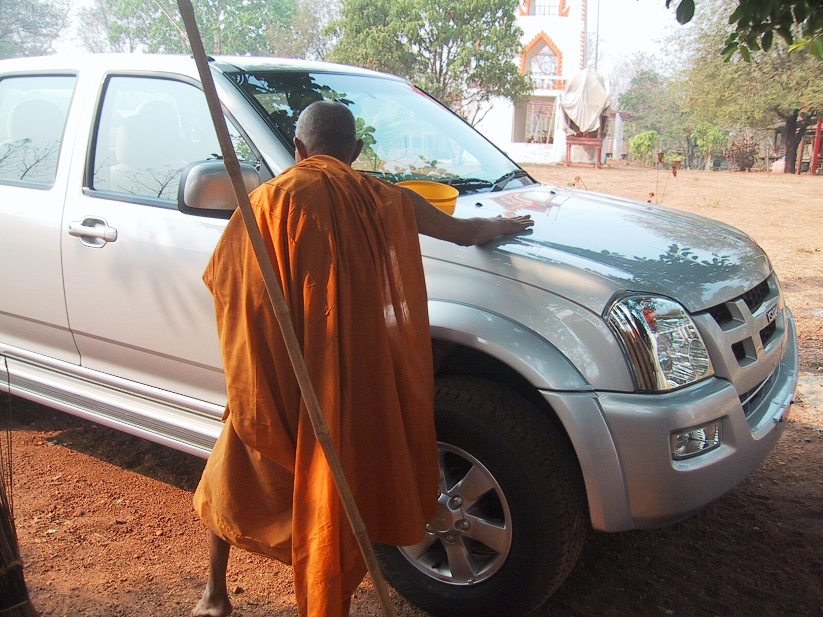 A monk blessing our pickup.  There is great discussion about which is the best Wat to get your motorbike or pickup blessed at, as they have different safety records.   They throw water on the vehicle and draw a strange complicated mandala on the roof lining