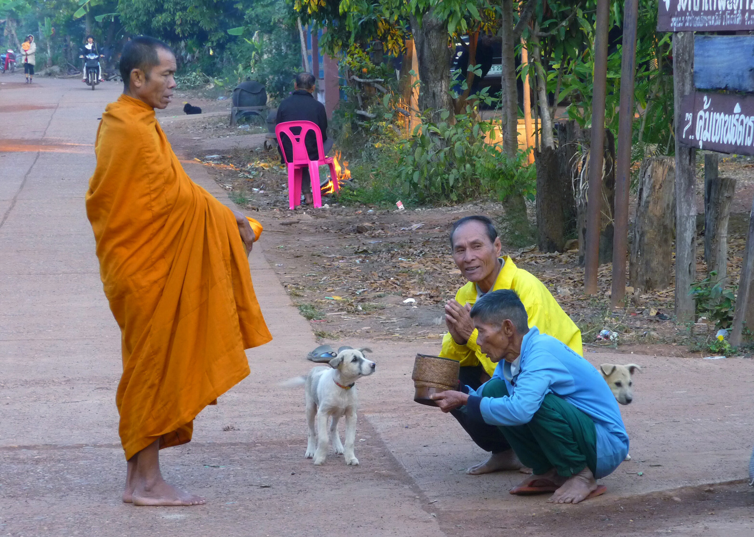 Giving alms to a monk on his morning rounds on a wintery day in our village in NE Thailand.  We take our guests to the village from our arts guest house Thailand-painting-holidays.com