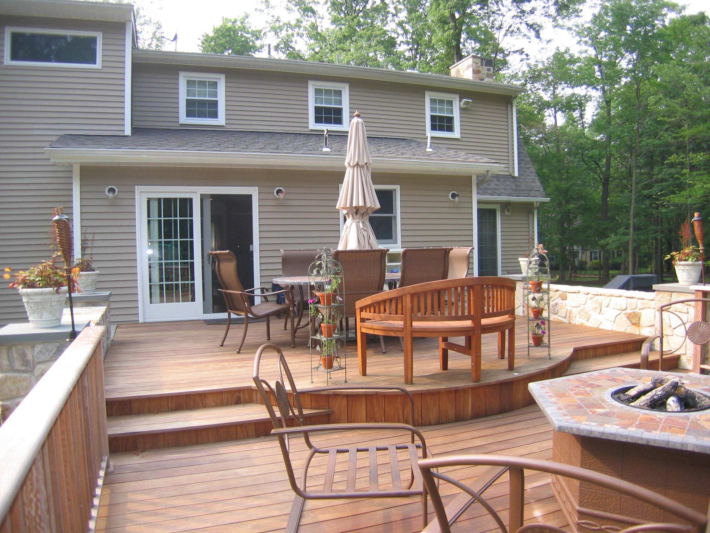 A two tiered deck with integral fire pit makes the kitchen addition beyond the true central focus of this Warren home.