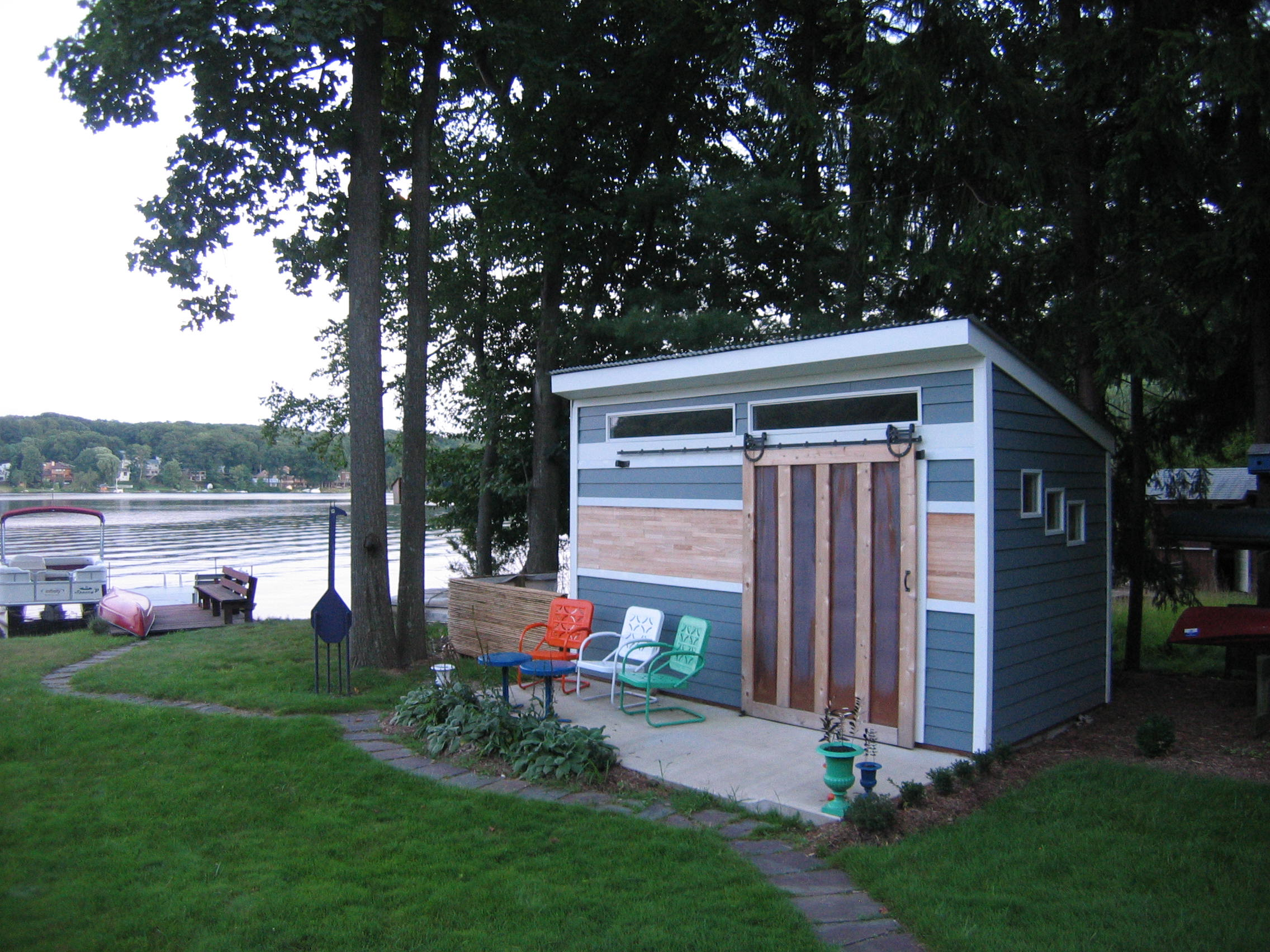 Distinctiveclients in White Meadow Lake sought a unique solution for a shed. Part boat-house, part green-house, part art-cottage. The view and sculptures complete the look.