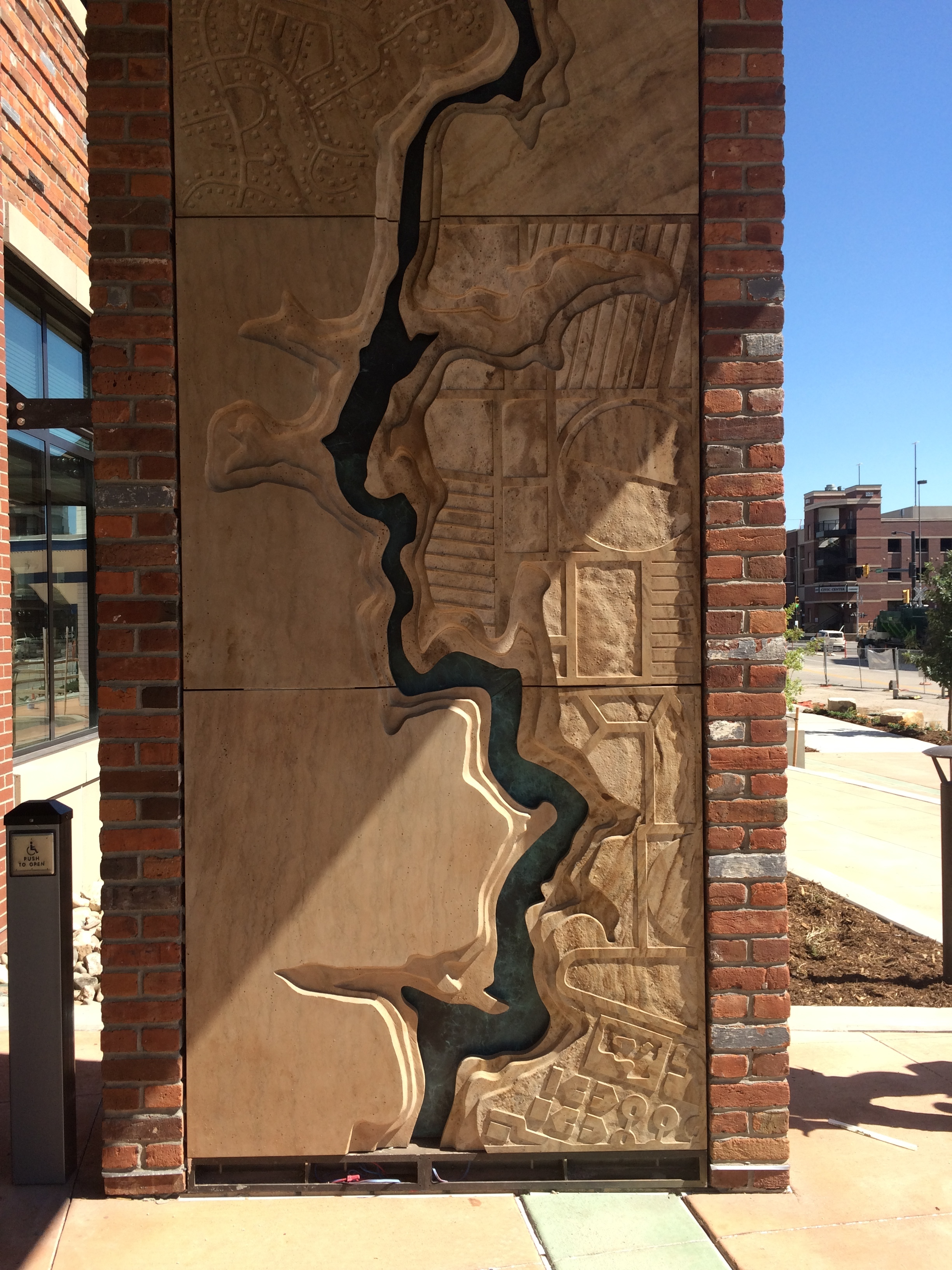 Entry feature wall with Poudre River topography,by Chevo Studios.