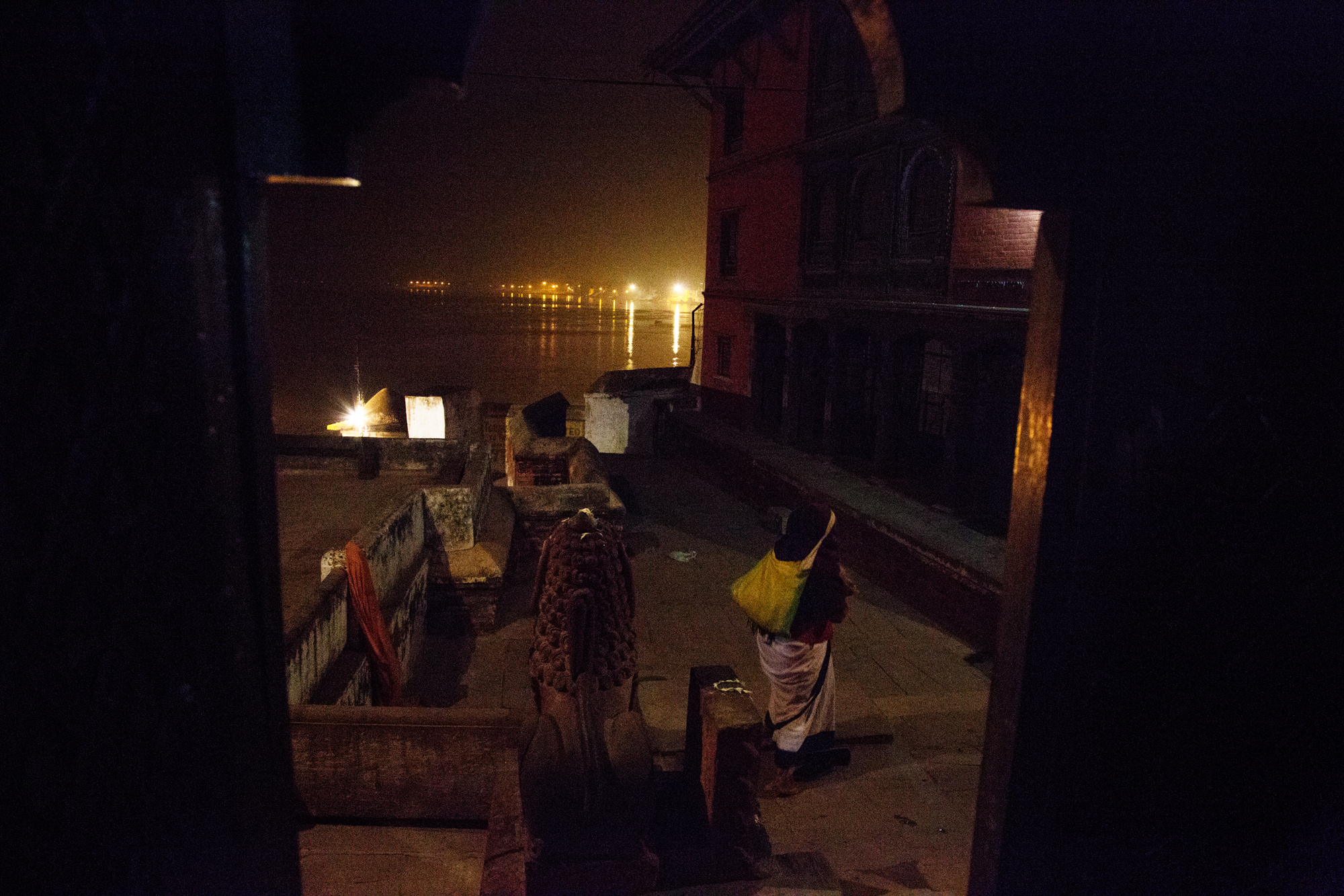 A woman leaves the temple to return to the ashram after evening Aarti.