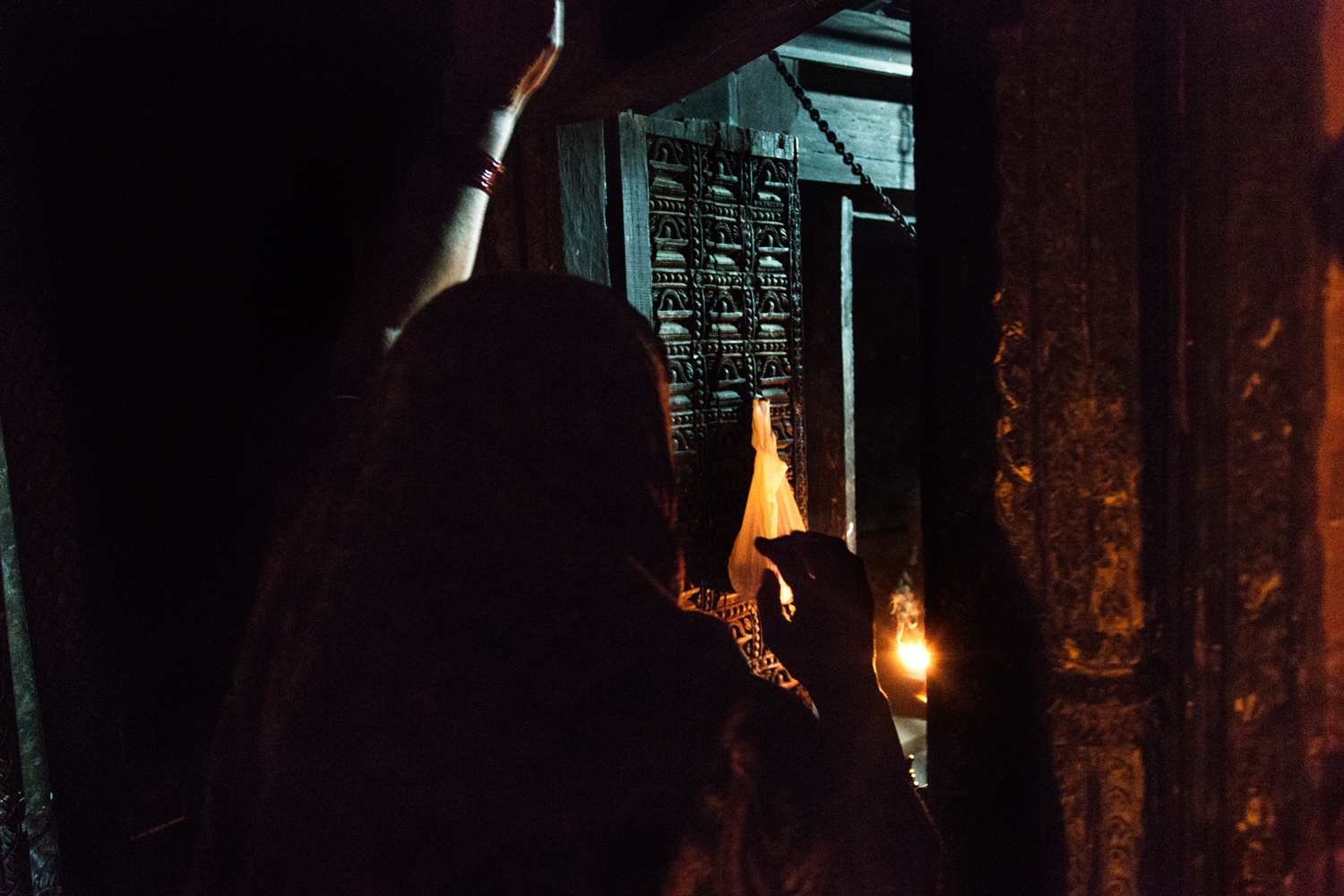 A woman rings a temple bell during evening Aarti. Bell ringing has an important significance during Aarti to welcome the gods into the idol so that devotees may be able to see his or her holy image in the ritualistic light.