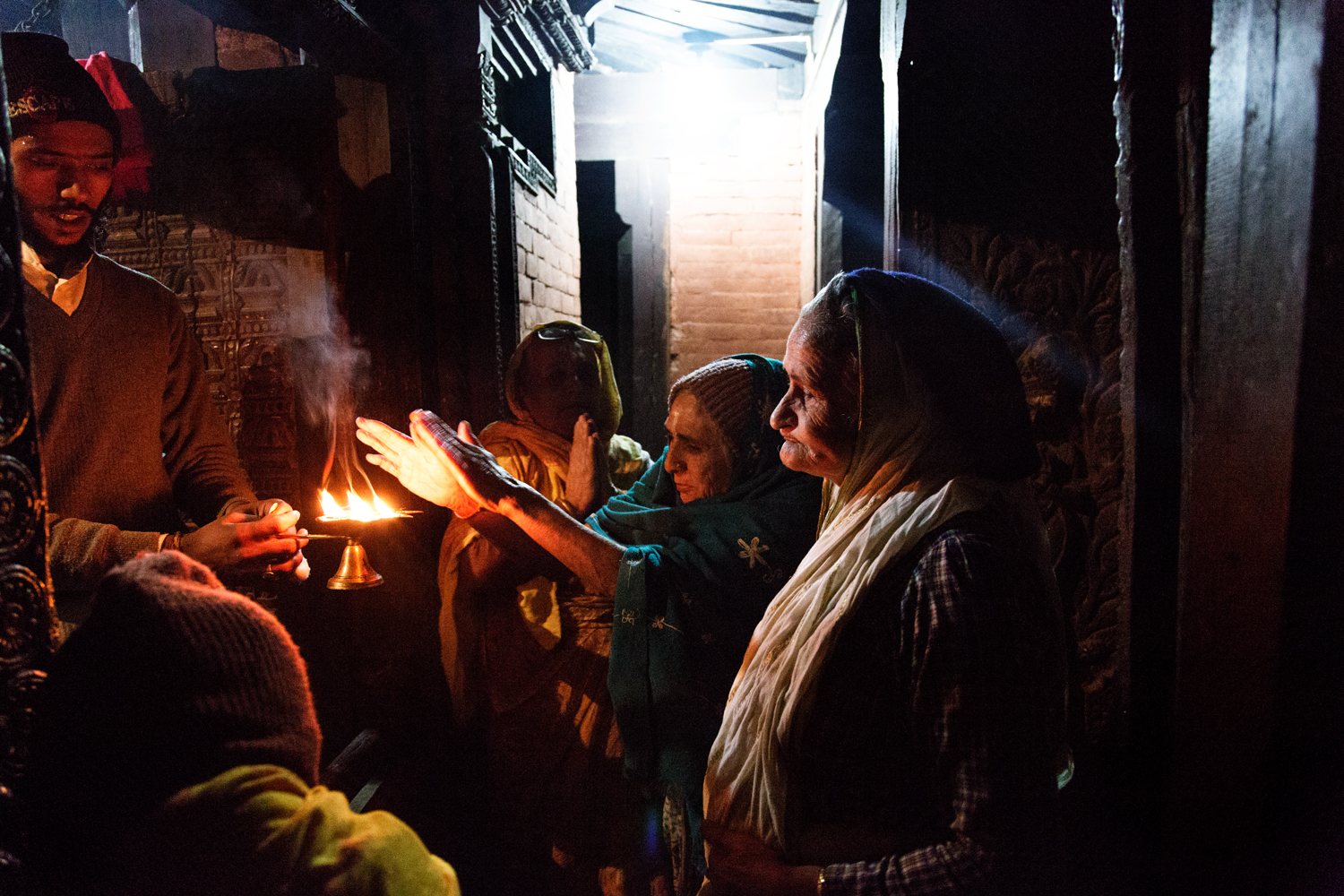 During evening Aarti after a period of prayer ceremonial fire is passed around to allow devotees to raise downturned hands to the flames to receive the flame's power, which they then press to their eyes and head, a purification and a blessing.