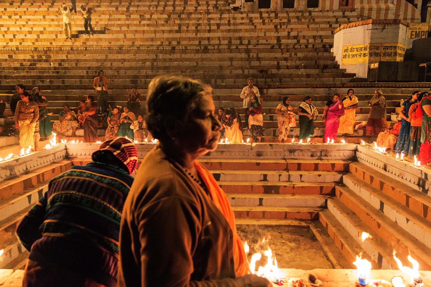 Women gather for evening prayer on a popular Varanasi Ghat by the River Ganga, in Uttar Pradesh India.