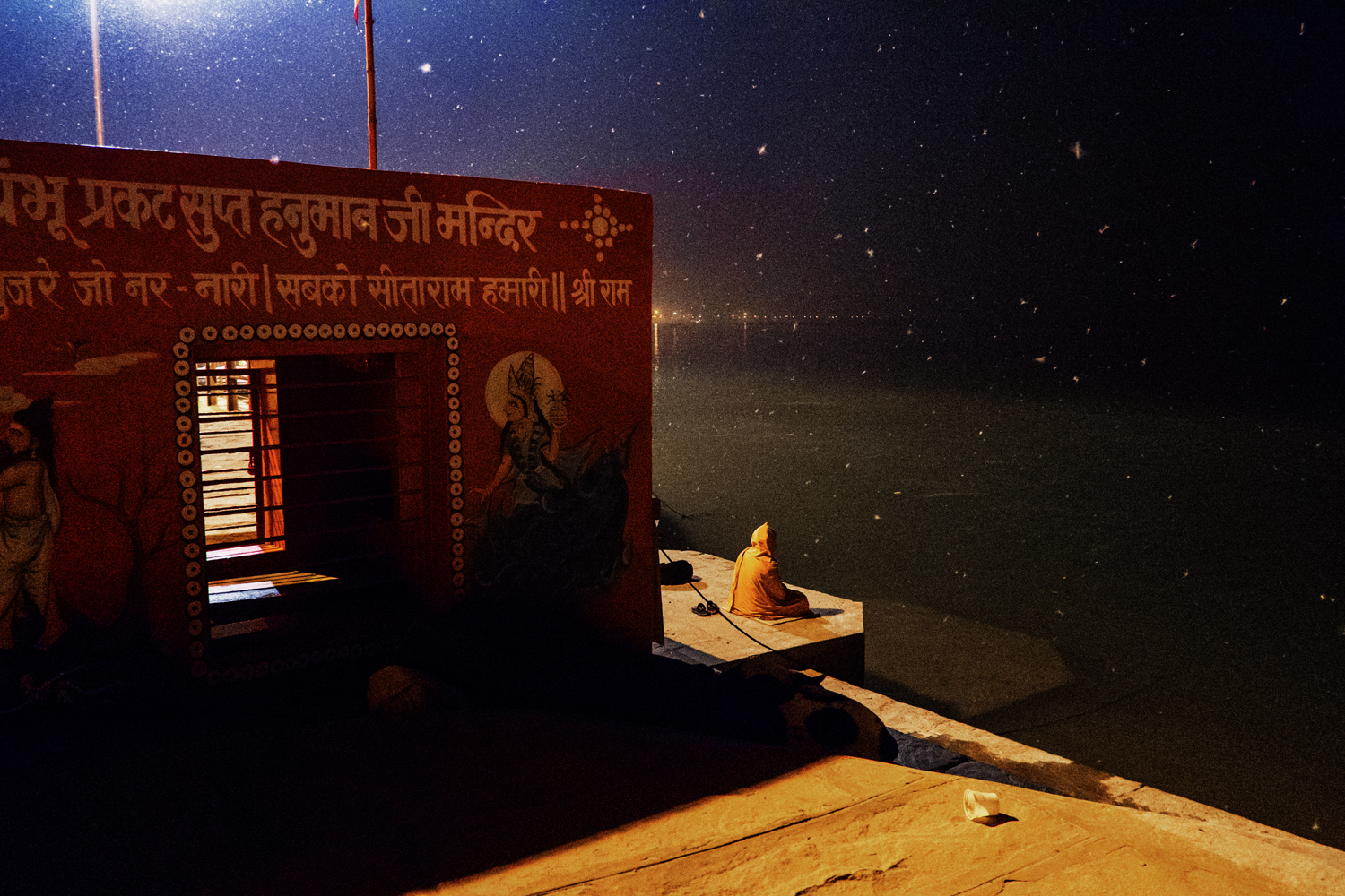 A devotee meditates in front of a small temple near Assi Ghat a cremation site overlooking the Ganga River. Thousands of devotees and pilgrims flock continuously to the holy city of Varanasi in Uttar Pradesh, India.