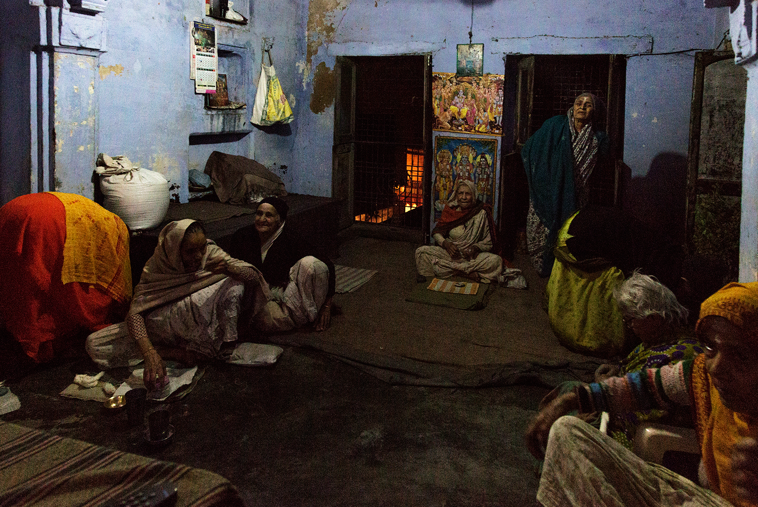 Women relax together and watch television in the ashram after evening Aarti.