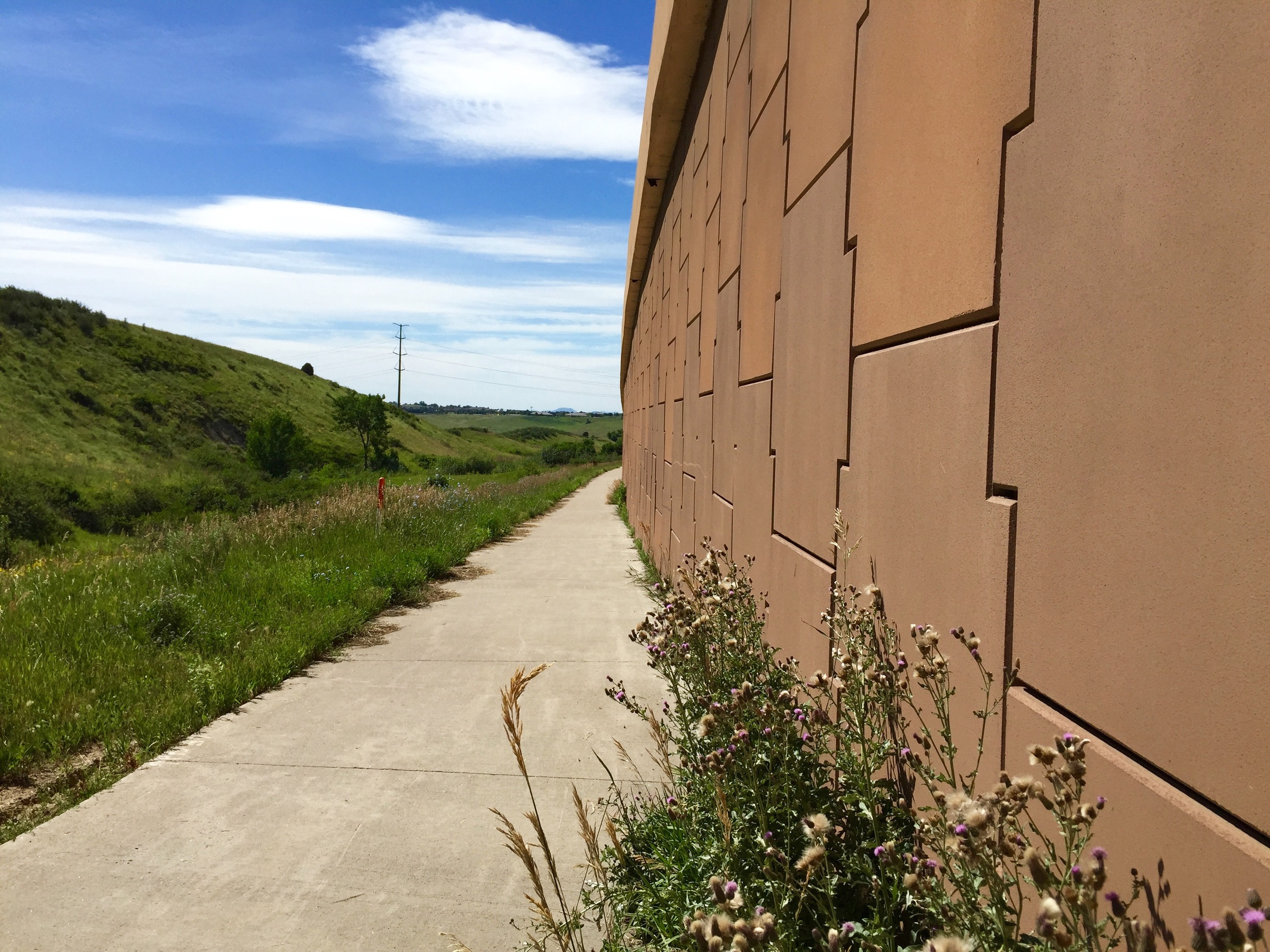 The urban and the wild each take a side of the trail along C-470