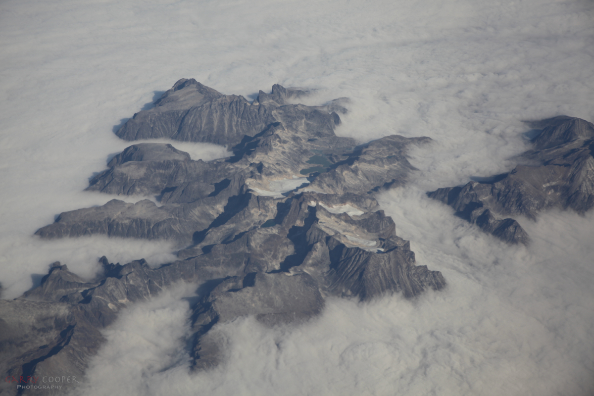 Mountain peaks poking through clouds, Greenland