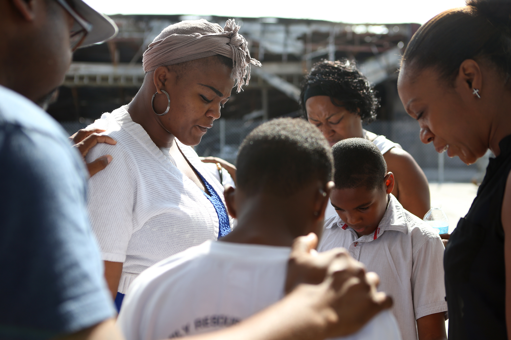 Leslie Petty (left) and Tracey Sherman (far right) lead a prayer outside the QuikTrip on W. Florissant Ave. on Friday, Aug. 15, 2014 after police released images from surveillance footage identifying Michael Brown as a suspect in a robbery shortly before he was fatally shot by police on Aug. 9, 2014. Earlier Friday morning, police also identified the name of the officer involved in the Michael Brown shooting.
