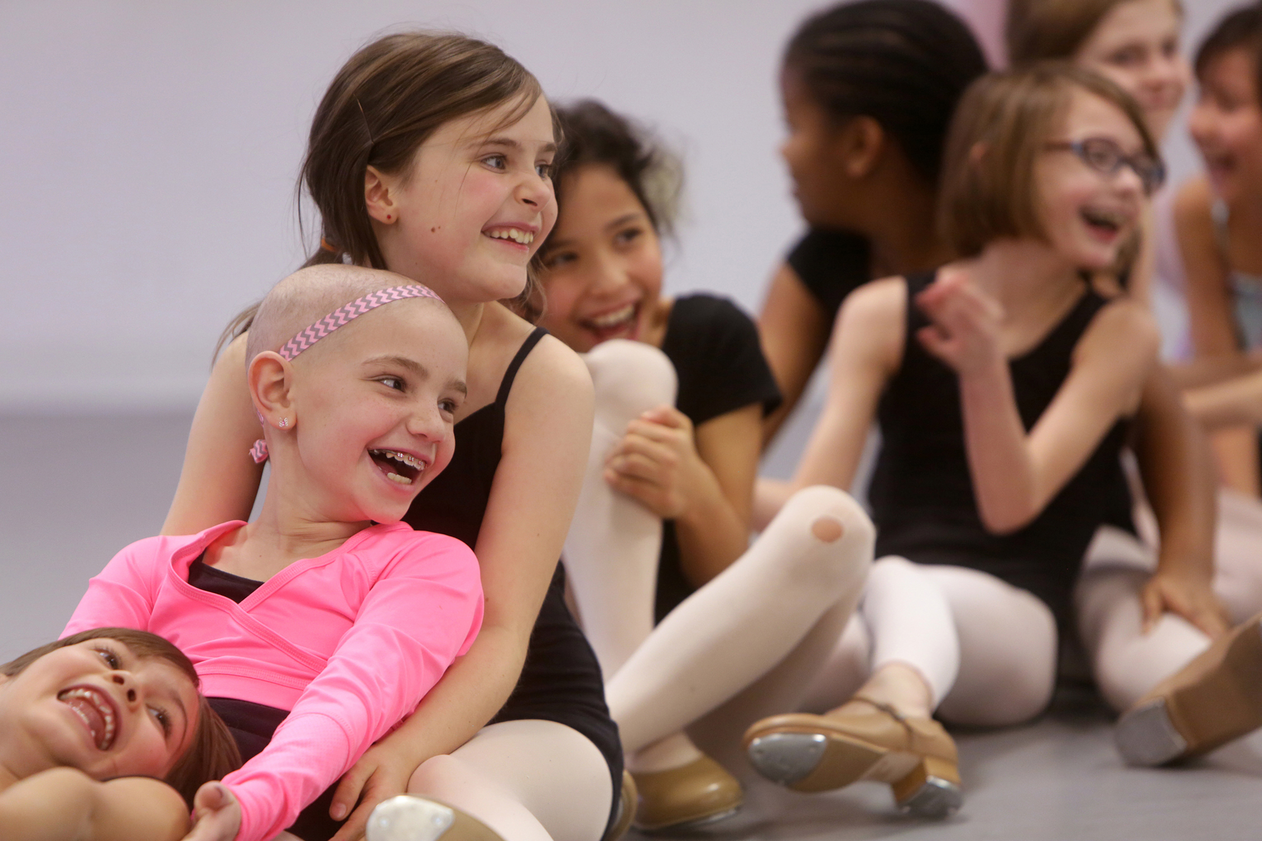 From left to right facing forward, Elena Bollman, 8, (lying down) Arianna Dougan 8, Madison Lamoureux 9, Anastasia Chostner, 8, and Madeline Miller, 8, (with glasses) laugh as they land after falling backwards as part of a dance number at St. Louis Academy of Dance in Olivette on Tuesday, Feb. 10, 2015. Dougan is currently undergoing treatments for neuroblastoma. When she was too sick to attend class, her teachers came to her as part of a dance therapy program.