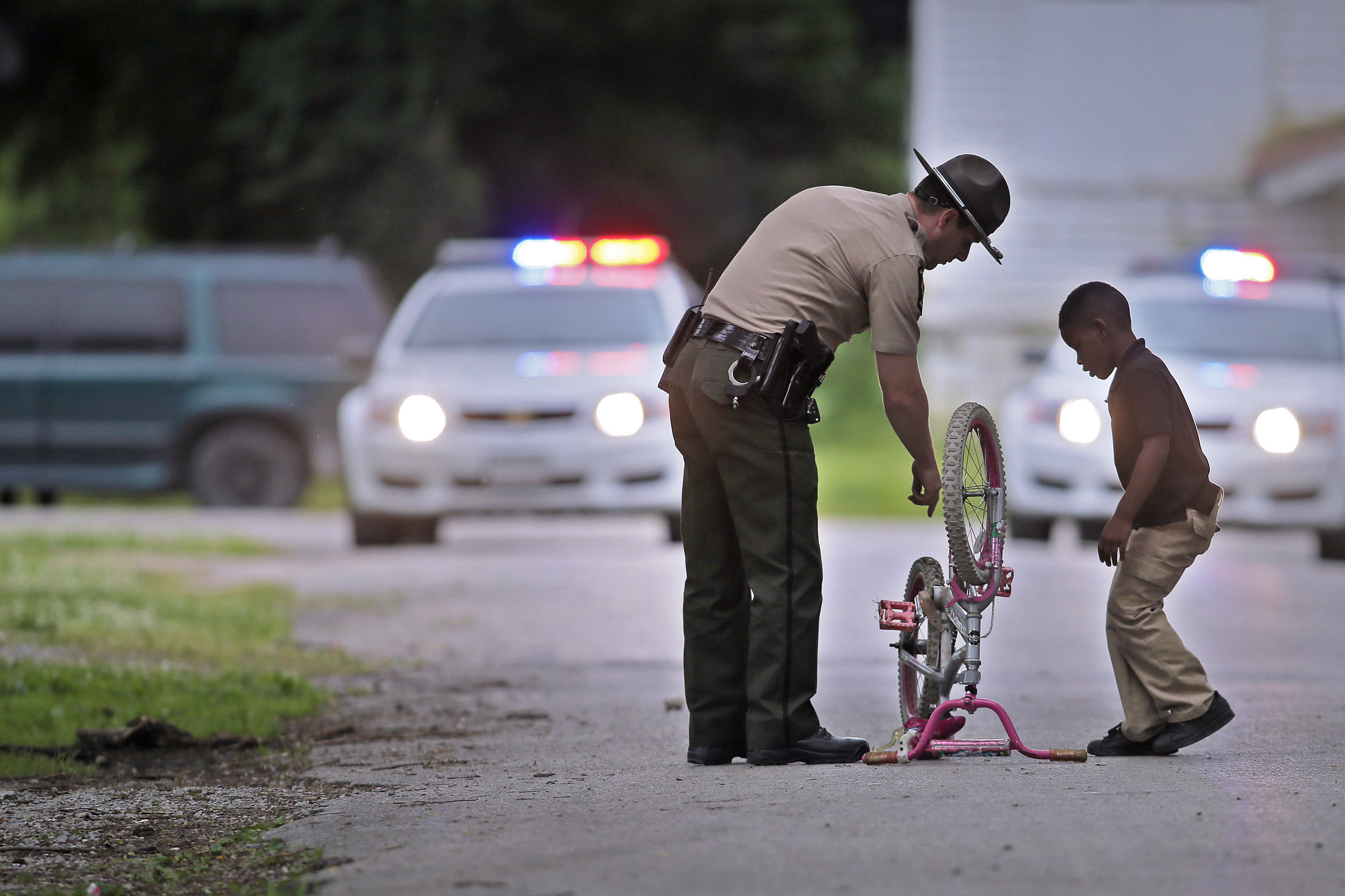 Illinios State Trooper Jeff Karns assists 6-year-old Arion Harrison with his bike as police investigate the scene of an officer-involved shooting in East St. Louis near Washington Park on Thursday, May 26, 2016. The man who police believe shot and killed a 21-year-old woman in a downtown St. Louis carjacking was shot and killed by officers in the Metro East Thursday afternoon, police said.
