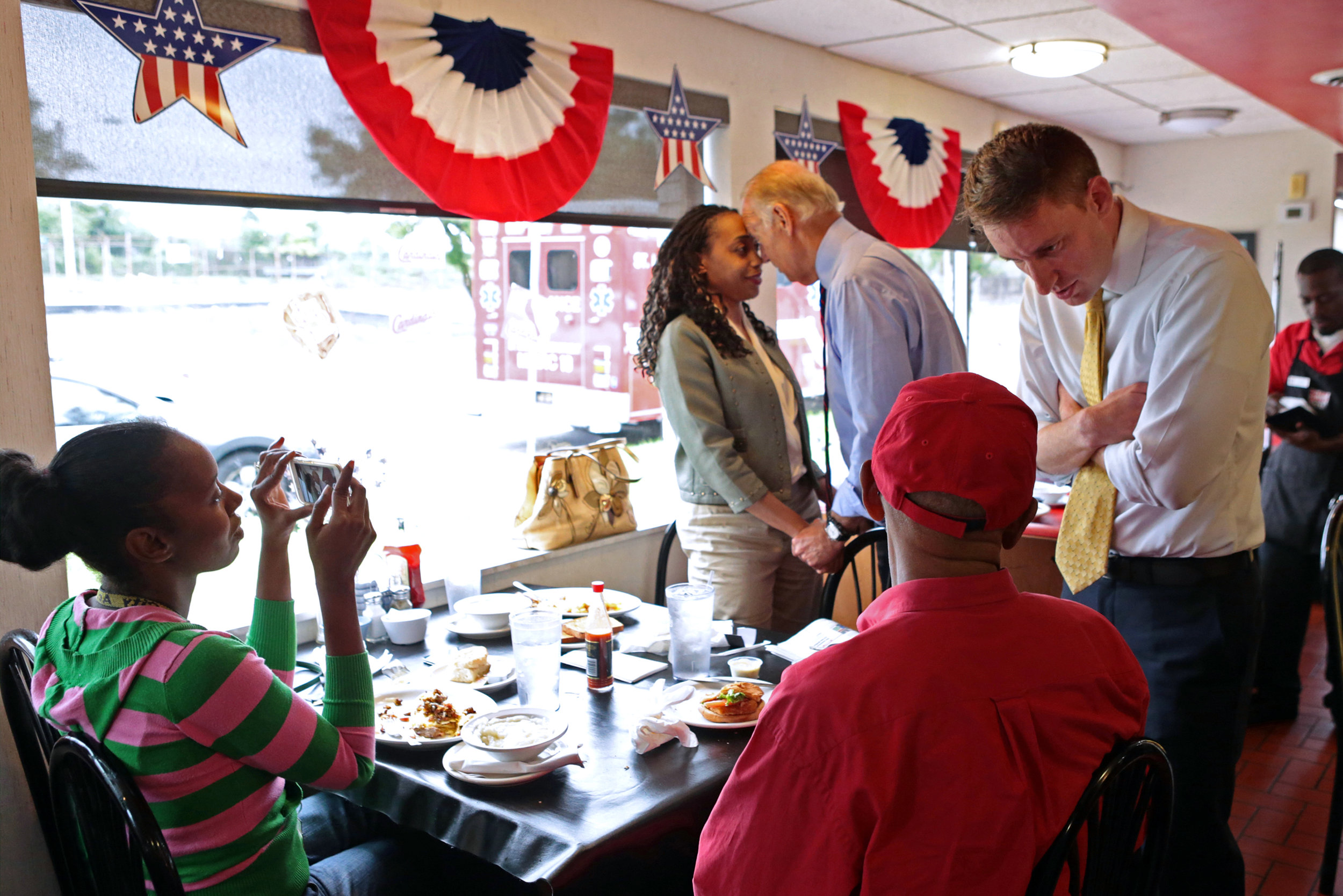 Missouri Secretary of State Jason Kander (far right) talks to Carl Bruce, of St. Louis, while Vice President Joe Biden greets Tina Grimes, of St. Louis, during a stop by Goody Goody Diner in north St. Louis on Friday, Sept. 9, 2016. Vice President Biden was in town to talk about technology and jobs creation at LaunchCode.