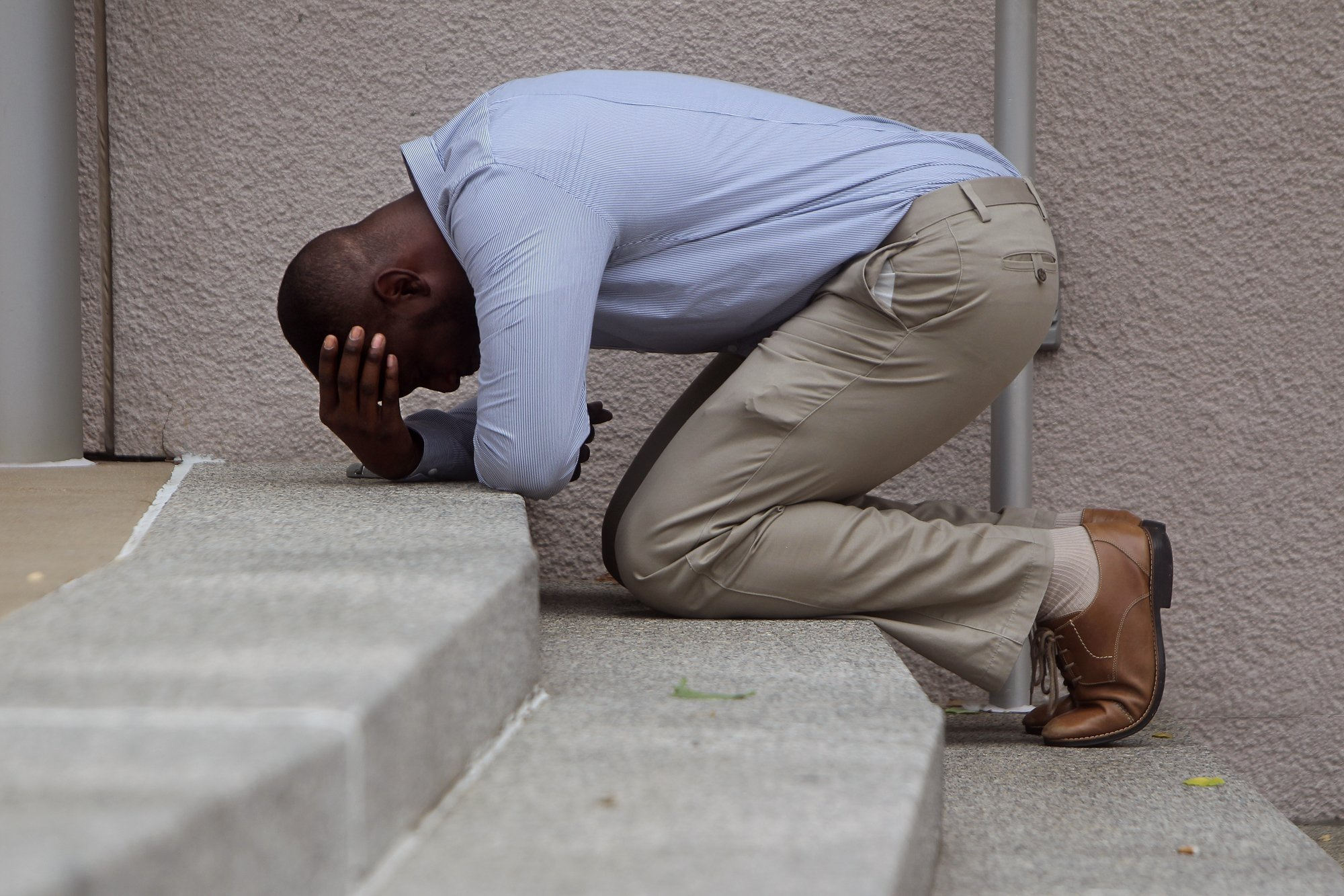 "Rev. Jonathan Tremaine, 34, of St. Louis, becomes emotional during prayer on the steps of Thomas F. Eagleton Courthouse as protesters and clergy members perform an act of civil disobedience as part of ""Moral Monday"" demonstrations on Monday, Aug. 10, 2015."