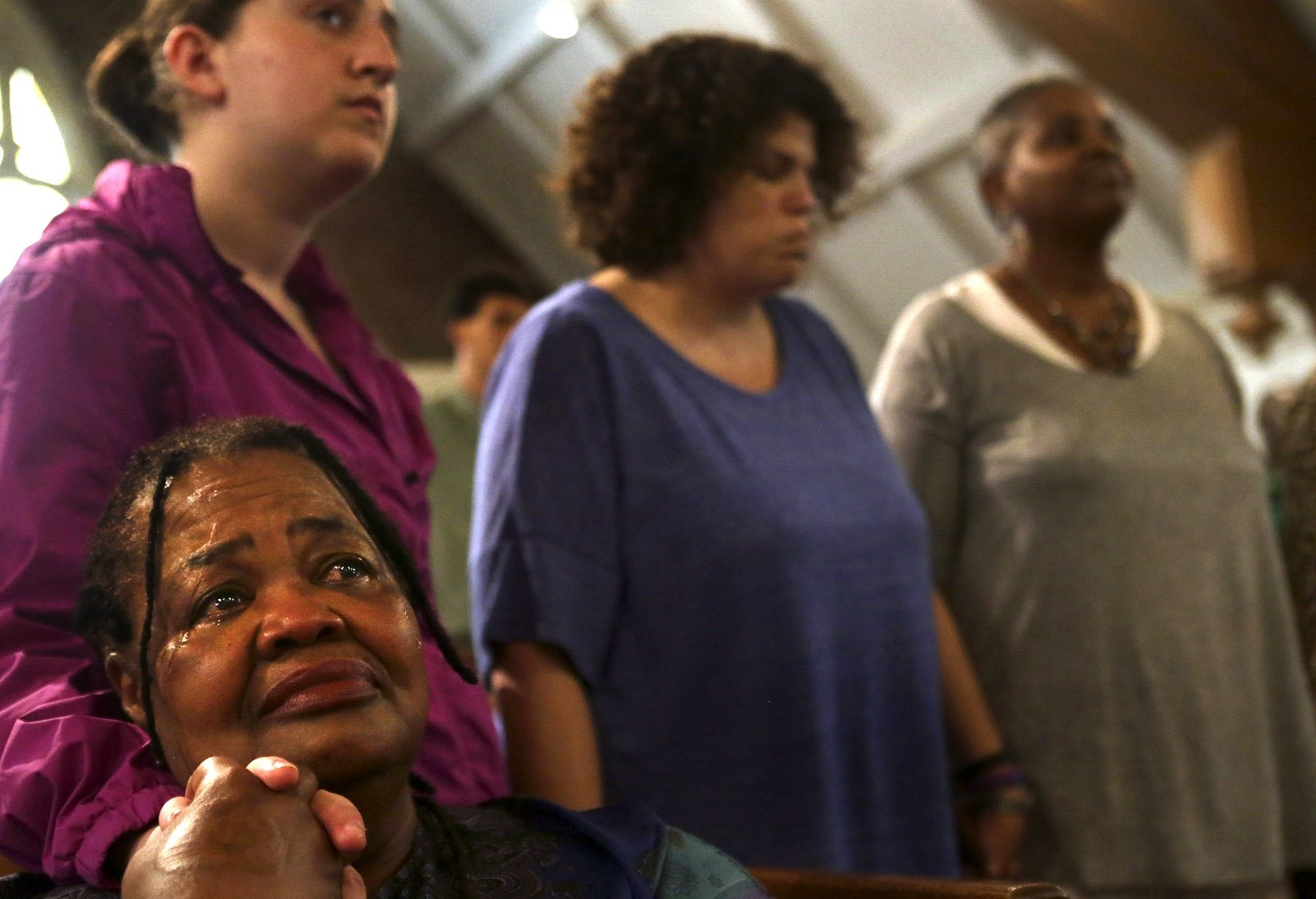 Romona Taylor Williams (bottom left) of St. louis, holds hands with 16-year-old Zoey Fleisher, also of St. Louis, during an interfaith prayer vigil for the victims of the shooting at Emanuel African Methodist Episcopal Church in Charleston, S.C. at St. Paul African Methodist Episcopal Church in St. Louis on Wednesday, June 17, 2015.