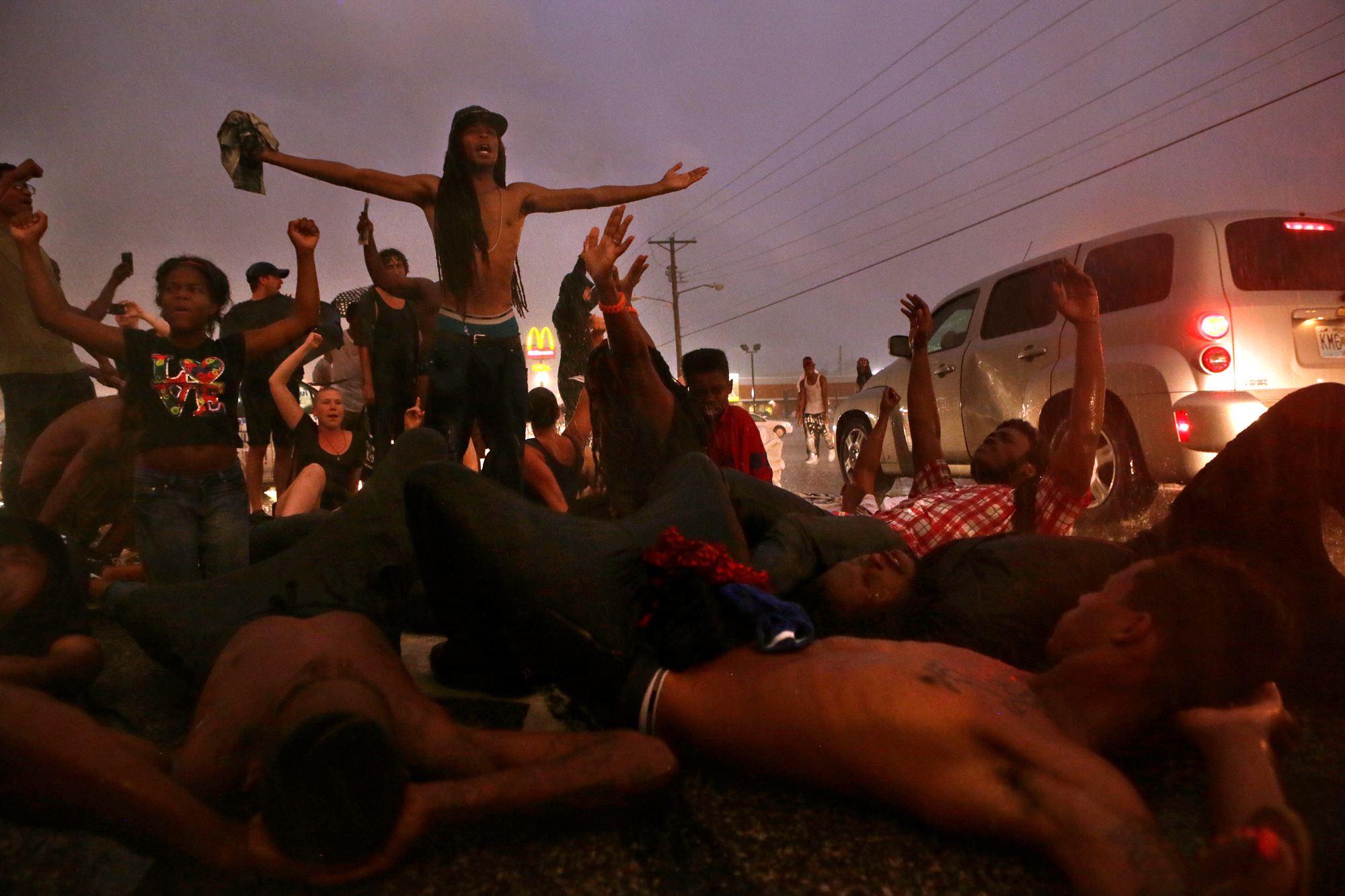 Protesters lie down in the middle of West Florissant Avenue as they demonstrate on the one year anniversary of Michael Brown's death by Ferguson police officer Darren Wilson on Sunday, Aug. 9, 2015.