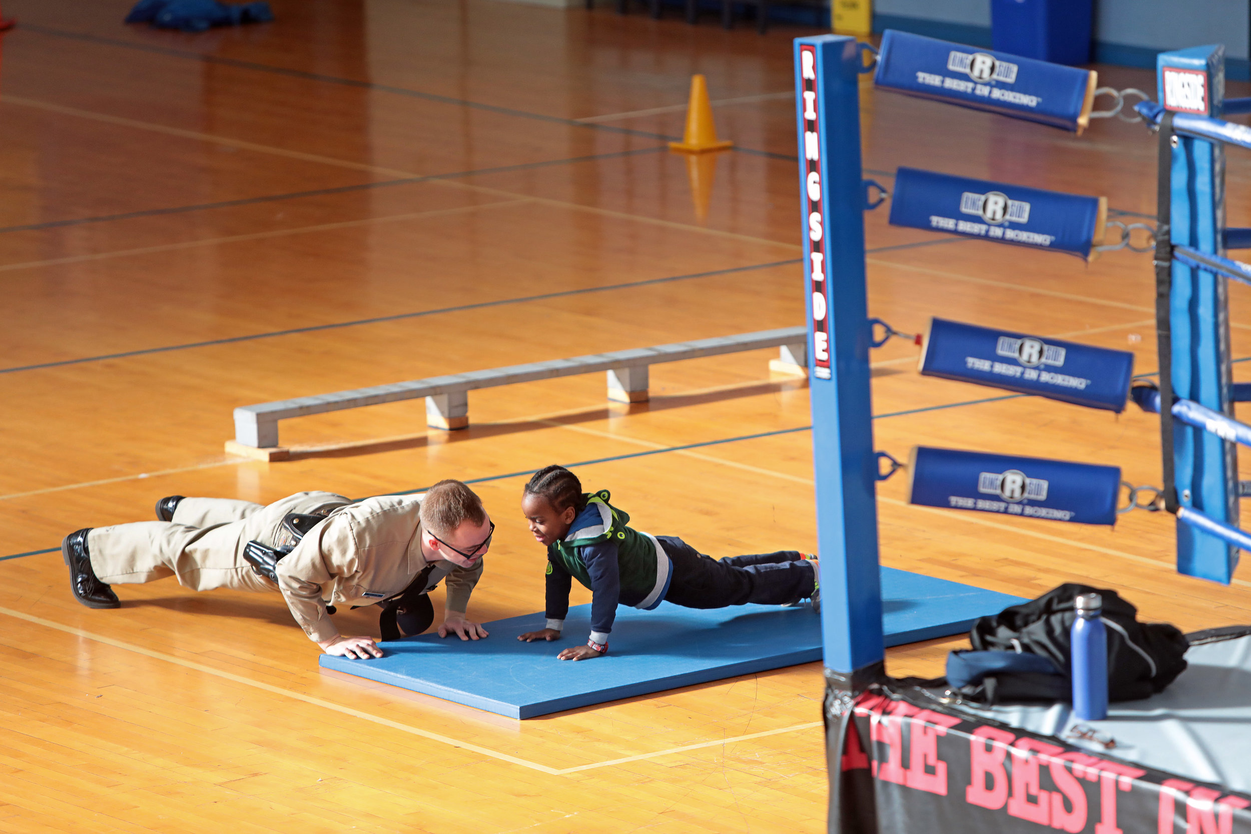 Police recruit Nate Wilson teaches 6-year-old Lazarus Baber, a student at Patrick Henry Downtown Academy, how to do a push-up during a visit to the St. Louis Police Academy as part of the Books & Badges program on Tuesday, Jan. 29, 2019. In the Books & Badges program, recruits are paired with students in the St. Louis Public School District and tutor the children once a week in reading and writing.
