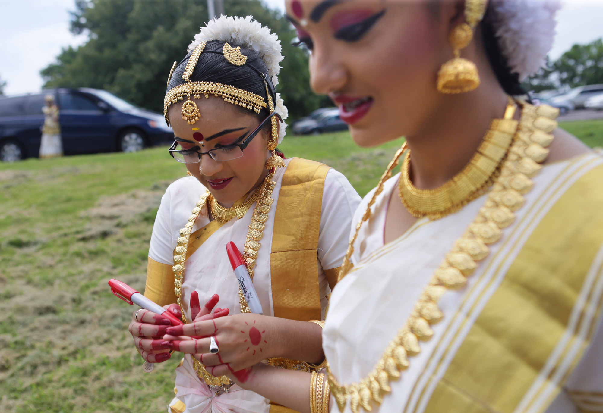 "Sruthi Ainapurapu, 13, (left), marks 16-year-old Varsha Kuchi's hands, before a performance at Queeny Park as part of Rath Yatra, or ""Chariot Festival"", which brings Hindu deities out in public on a chariot to expose people to the religion on Sunday, July 26, 2015. The festival began at the Hindu Temple of St. Louis in Ballwin and ended in Queeny Park."