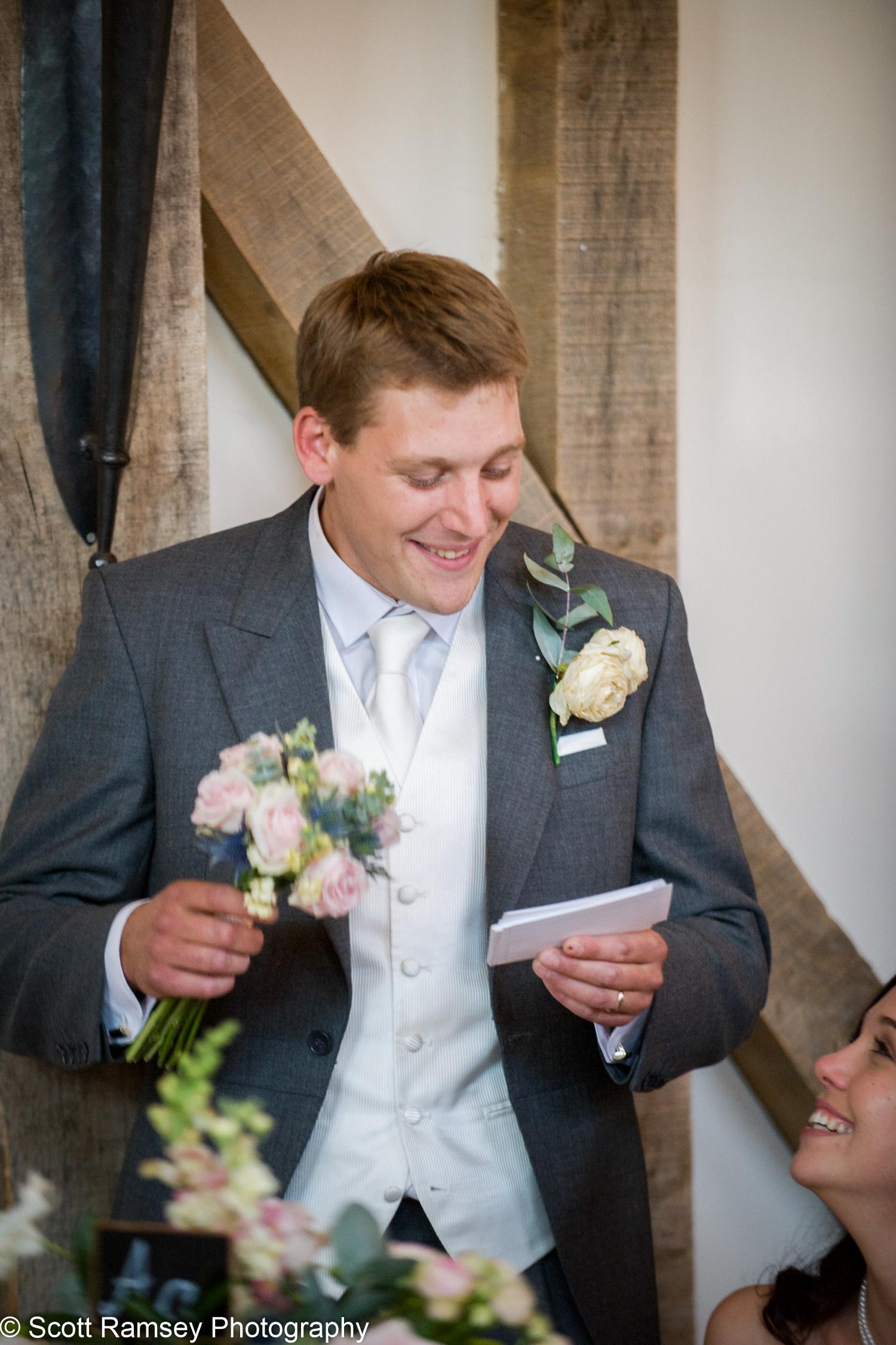Groom Holds Wedding Flowers Gate Street Barn