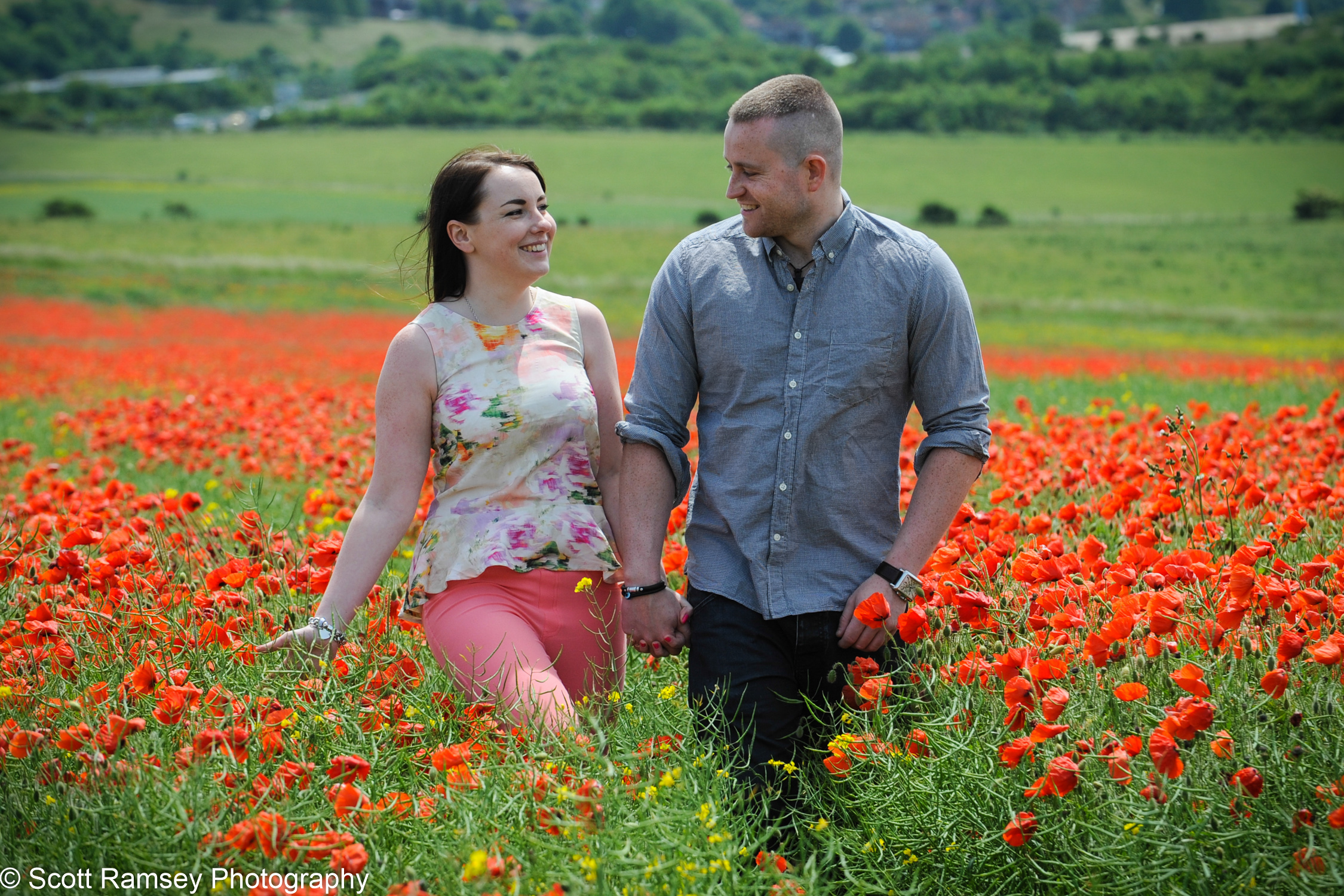 Matt and Chloe walking through a poppy field hand in hand during their engagement photography shoot. The photographs were taken in a poppy field on the South Downs North of Brighton in East Sussex.