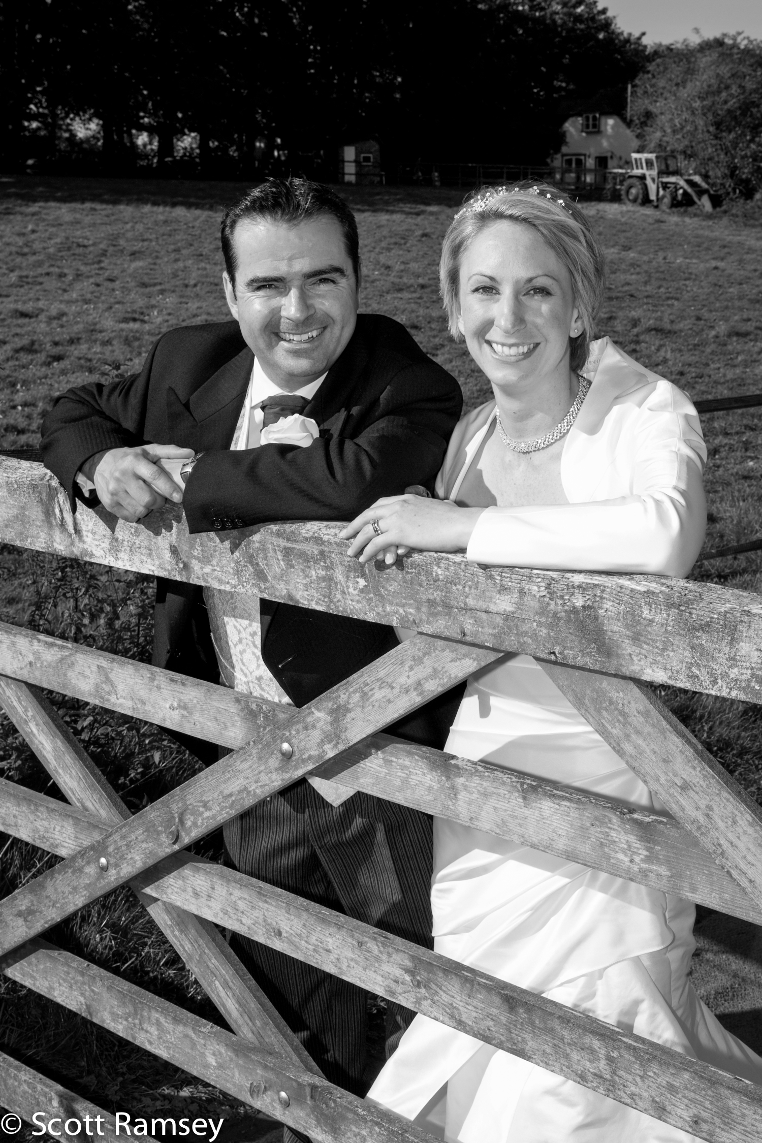 Bride And Groom Lean On Gate