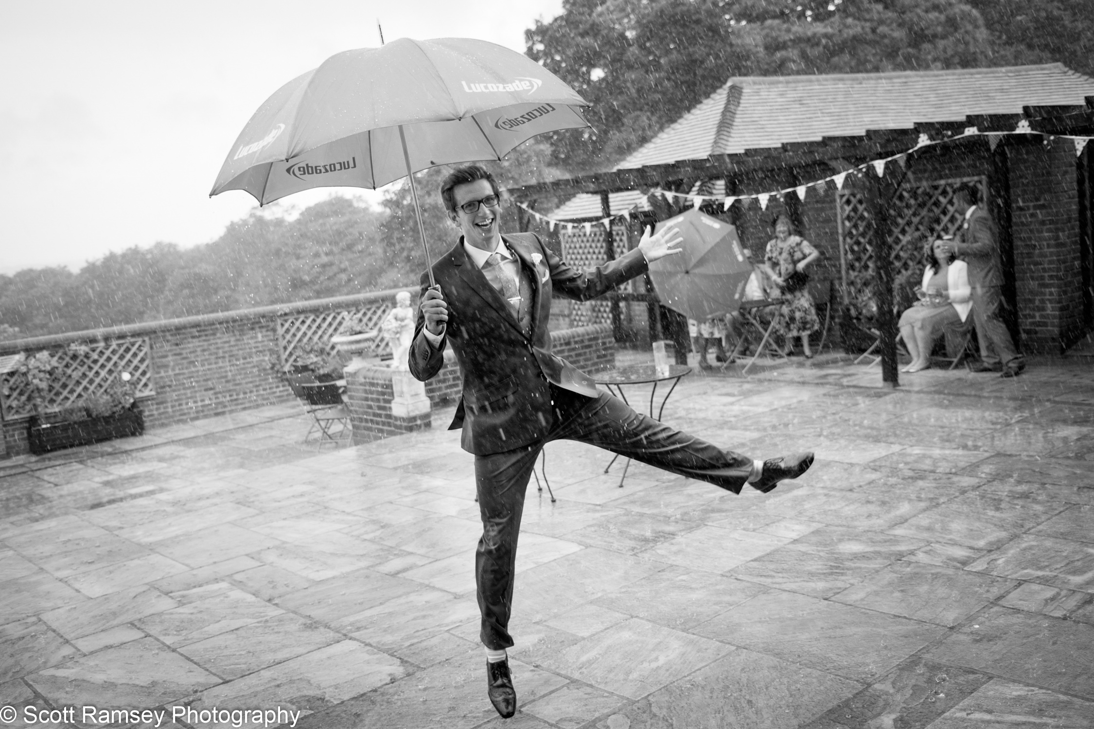 A groom dances in the rain during his wedding at Blackstock Farm Barn in East Sussex.