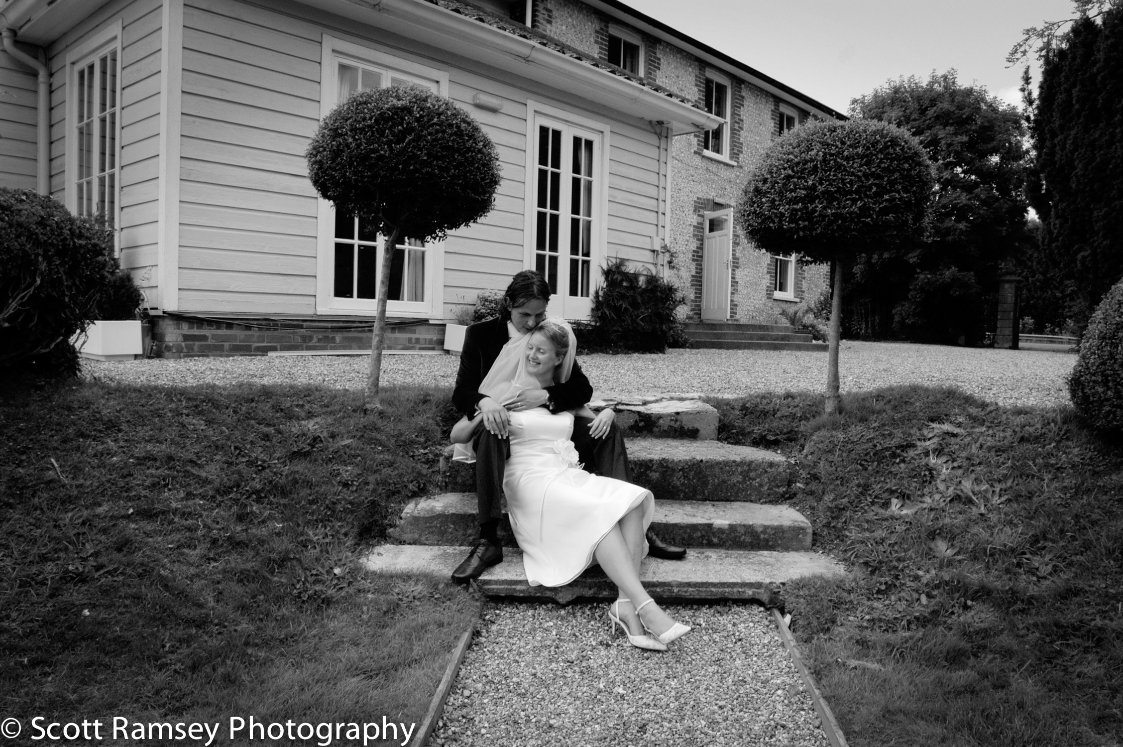 A Fontwell Park Wedding Photograph - A groom cuddleshis bride as they sit on steps in front of Fontwell House, Fontwell Park in West Sussex.