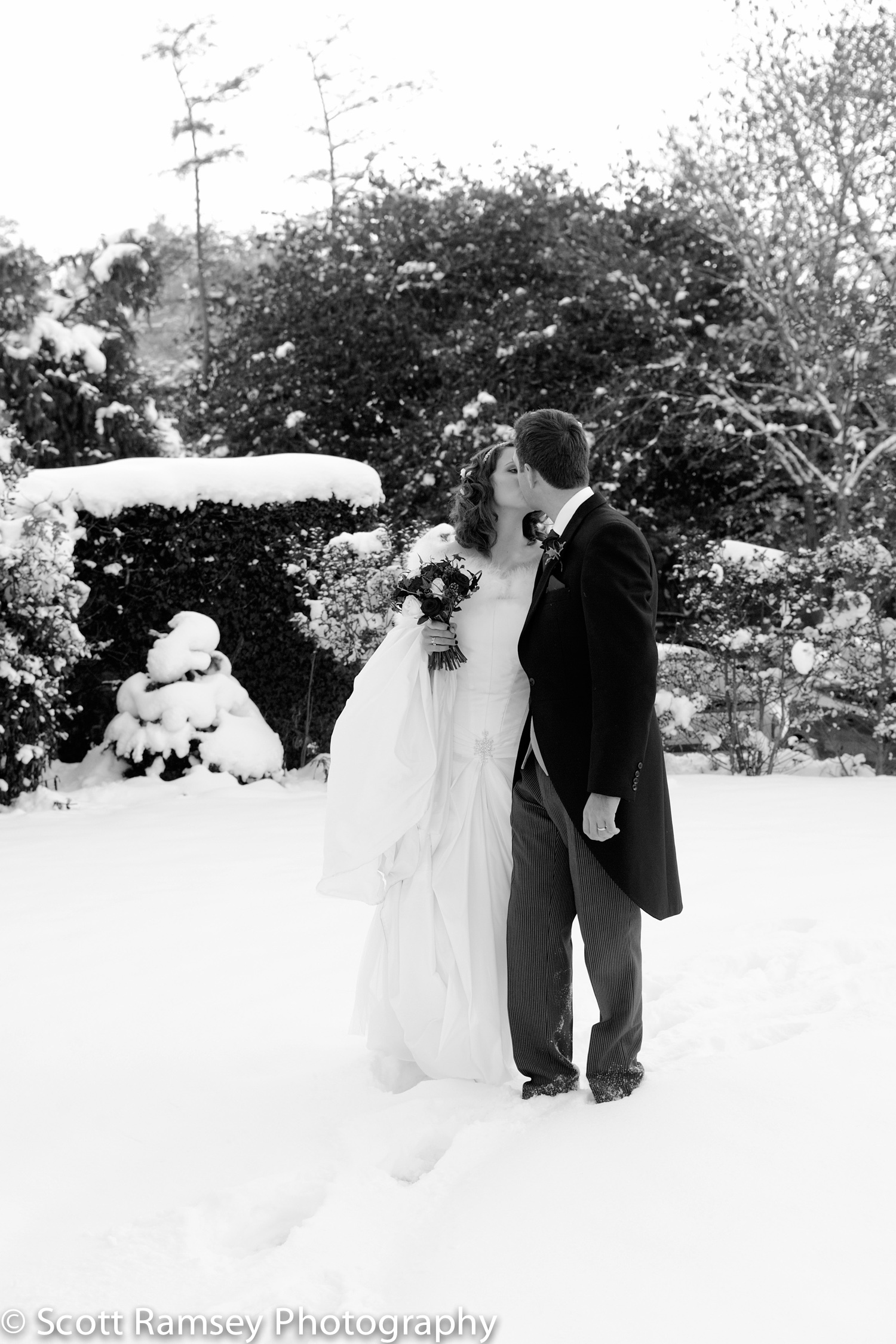 A winter wedding at the Spread Eagle Hotel in Midhurst in West Sussex. In this romantic photograph a Bride and Groom kiss as they walk through deep snow in the grounds of the hotel.