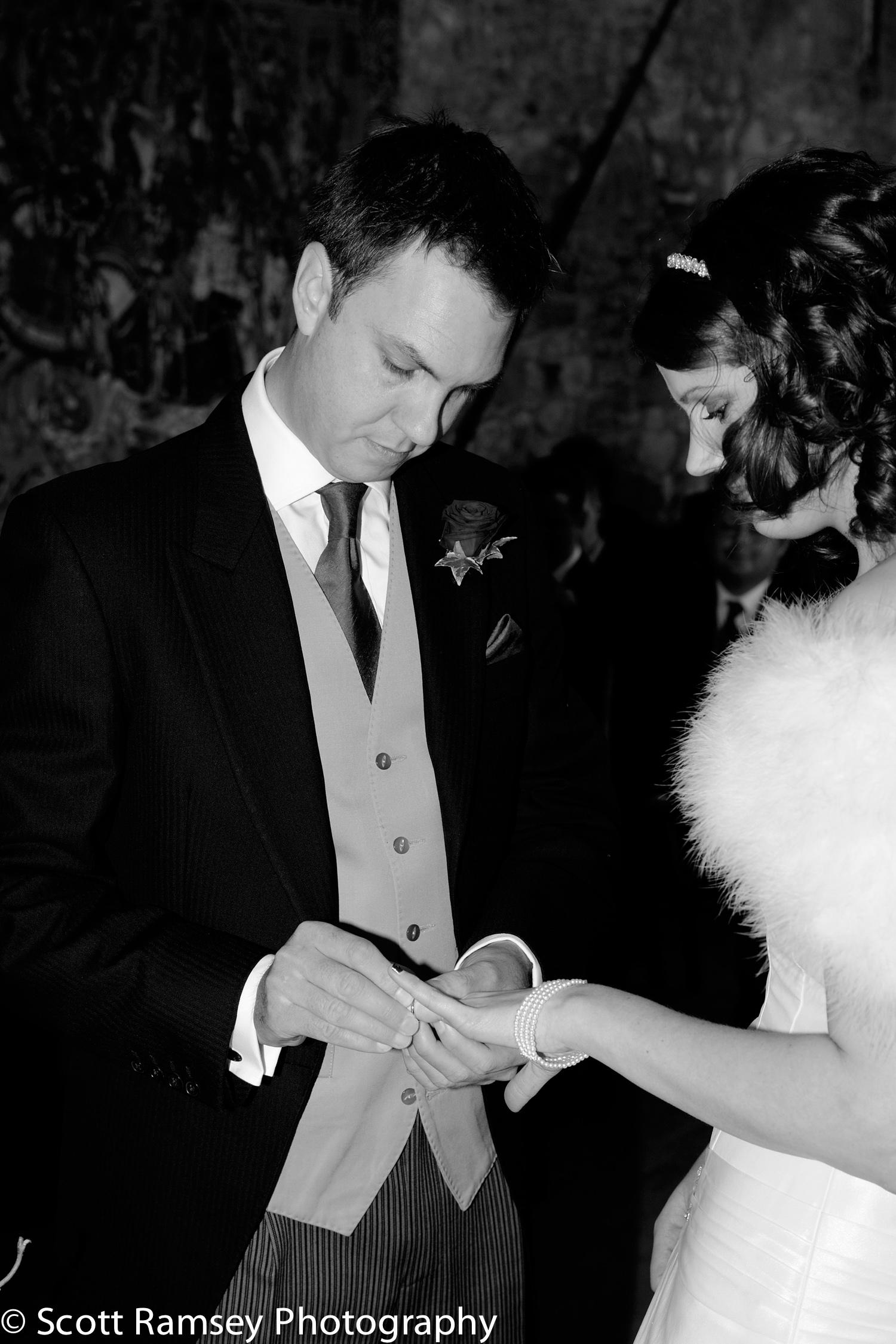 Winter-Wedding-Spread-Eagle-Hotel-Midhurst-Groom-Puts-Ring-On-Br