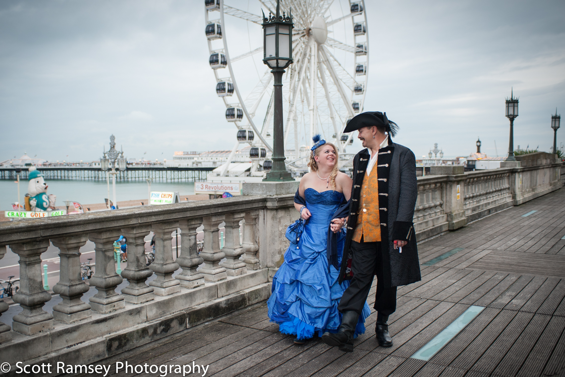 Wedding Photography in Brighton. A very fun Pirate themed wedding in Brighton, East Sussex. In Pic; The Bride and Groom (Dressed as a Pirate) walk hand in hand past the wheel on the seafront in Brighton.