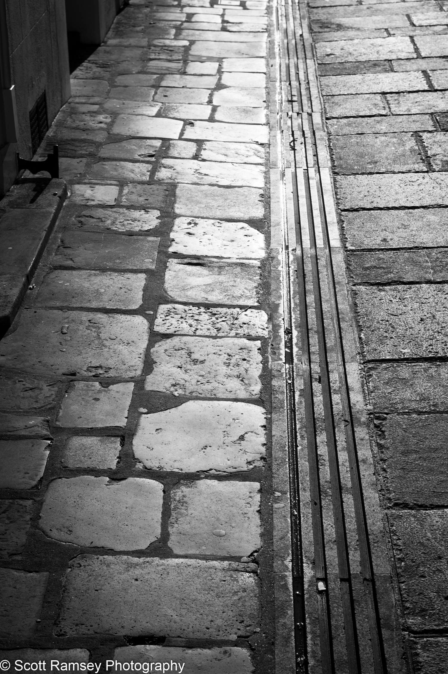 The winter sun reflects light on a wet cobbled street in Chichester, West Sussex, UK.