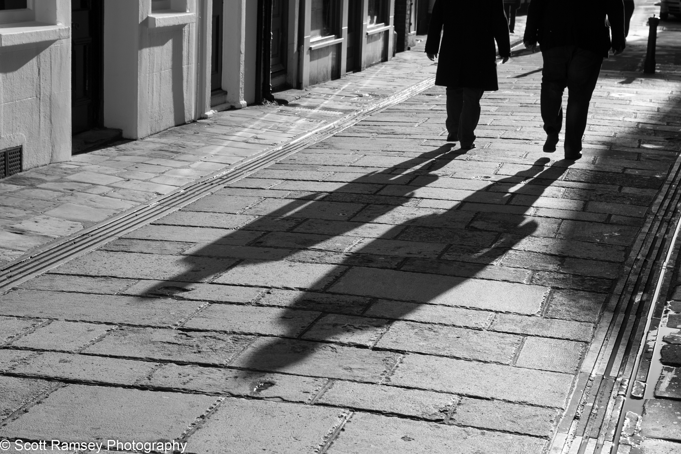People cast long shadows in the winter sun as they walk along a street in Chichester, West Sussex, UK.