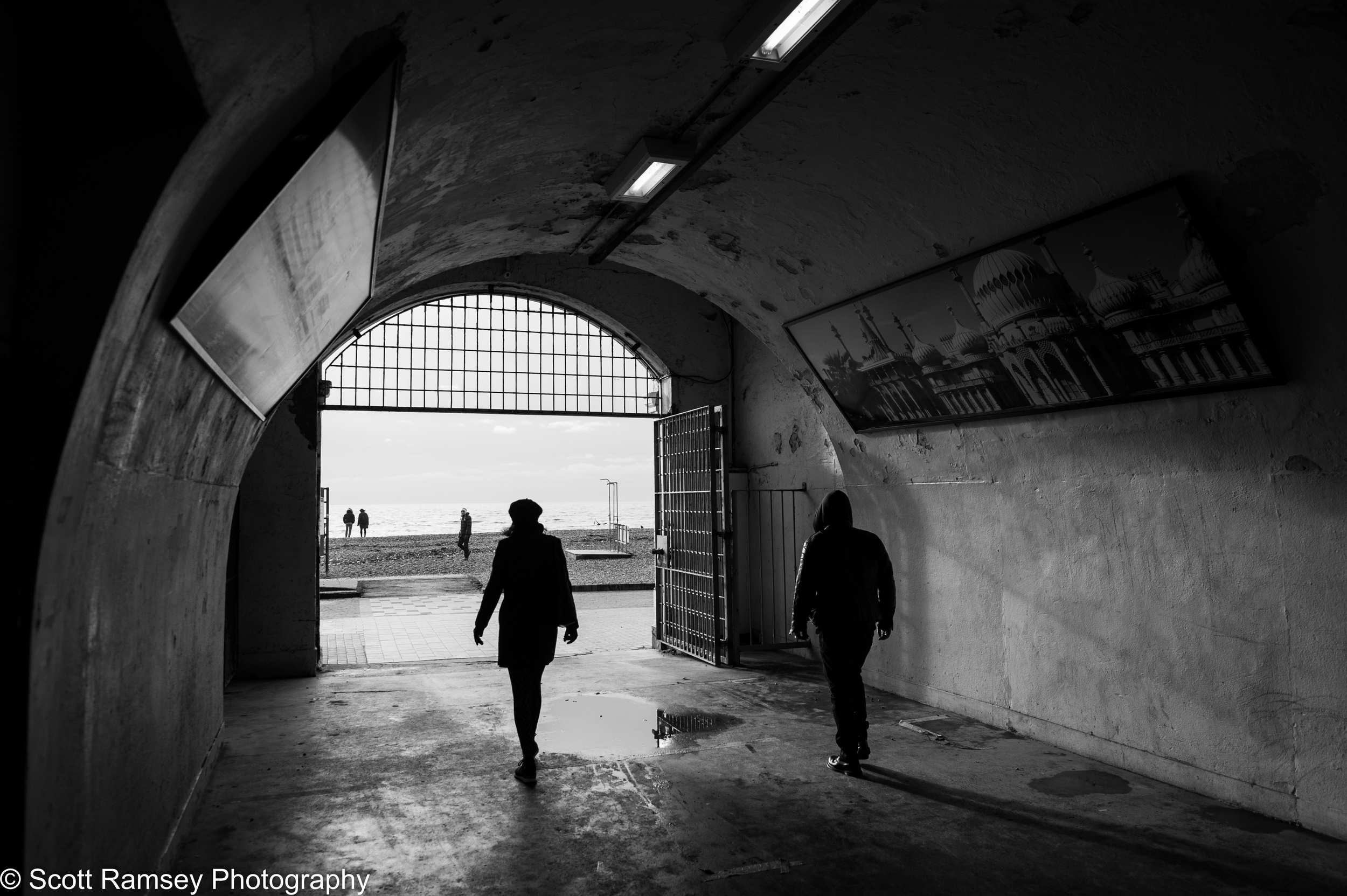 People are silhouetted against the winter sun as they walk through a tunnel that leads onto the beach on Brighton Seafront, East Sussex, UK. An old poster showing the The Royal Pavilion is on the wall above their heads. Photo by Scott Ramsey Photography