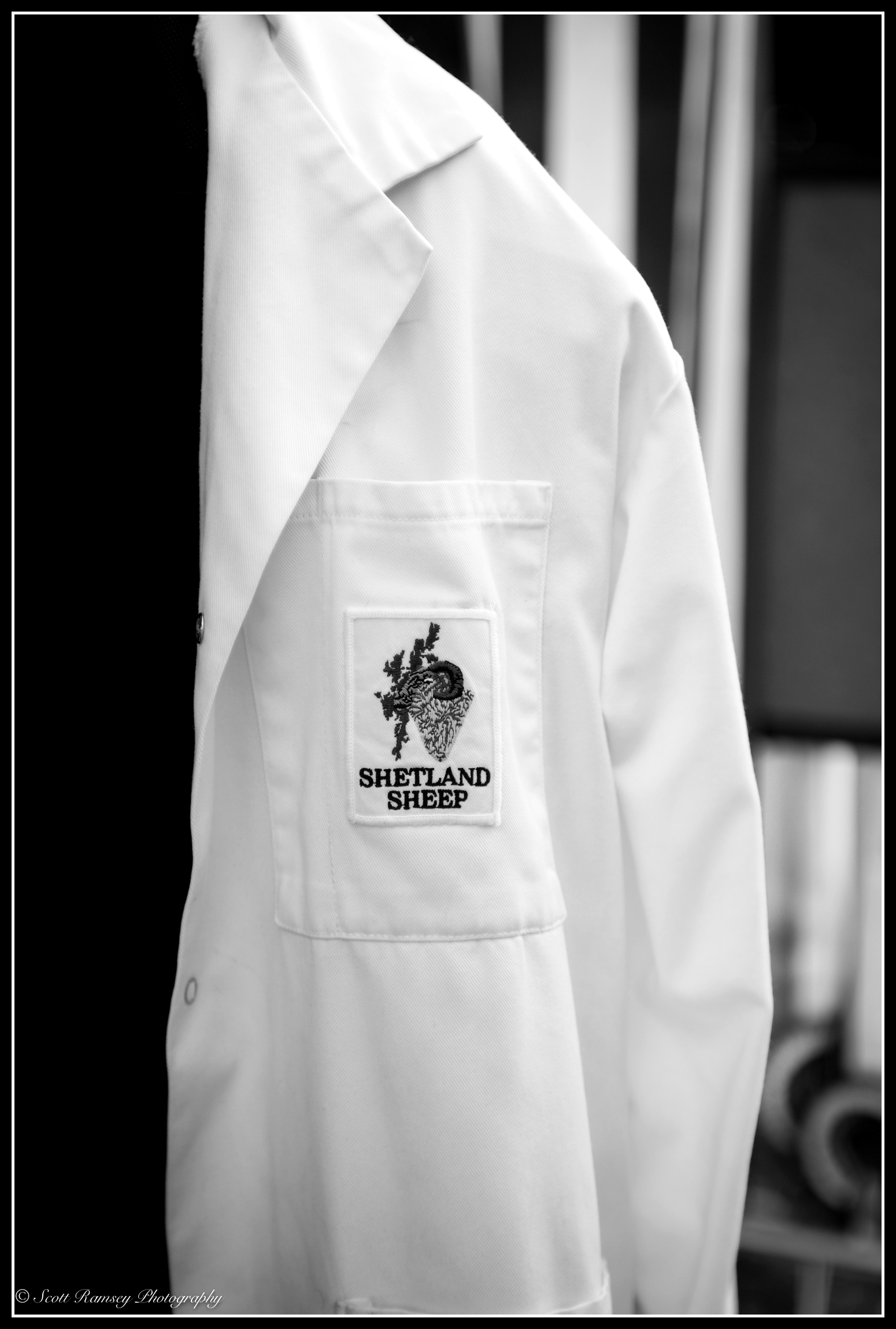 A white coat with a Shetland Sheep badge on it hanging up at the Findon Sheep Fair in West Sussex.