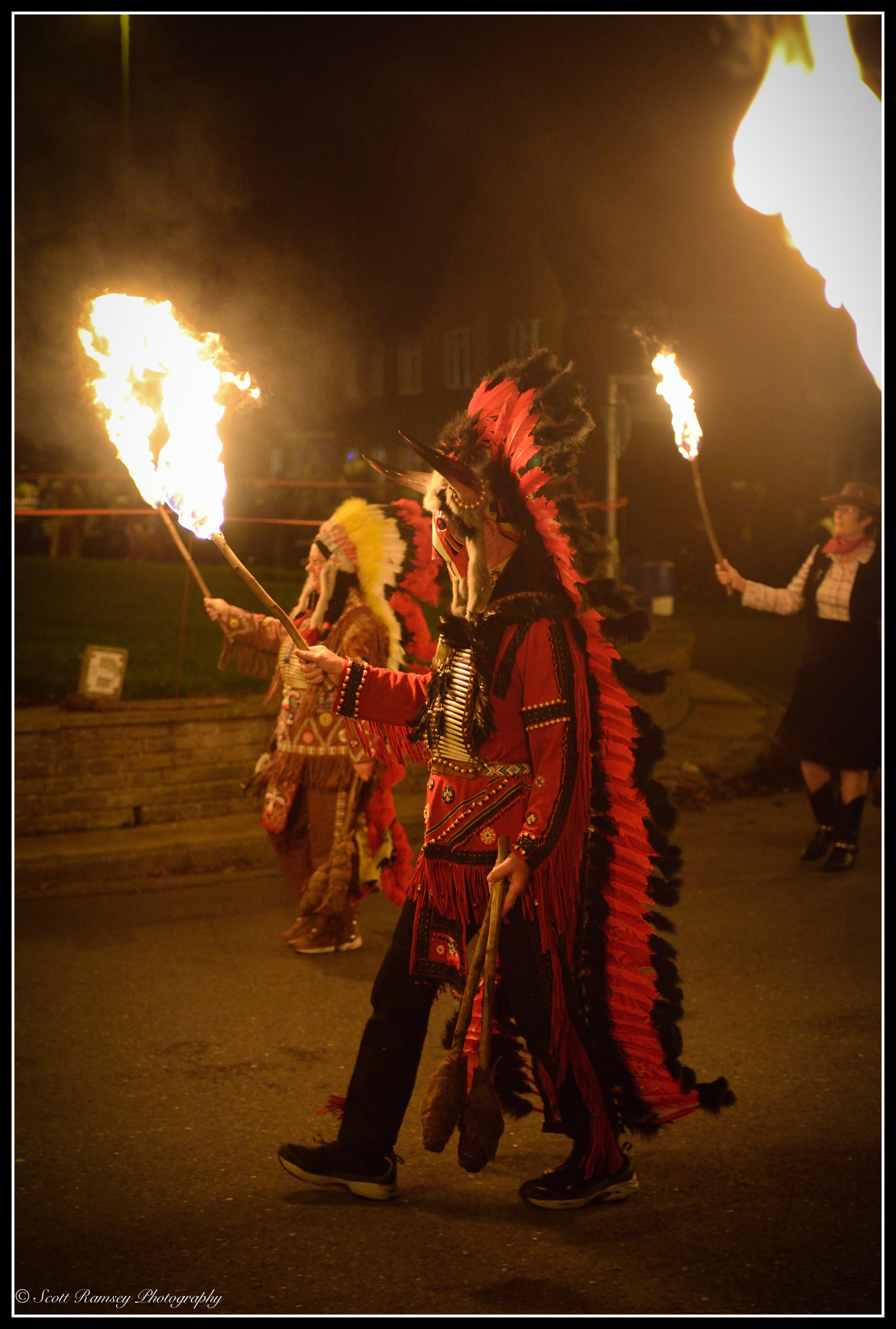 Members of the Littlehampton Bonfire Society dressed in North American Indian costumes hold flaming torches as they lead the procession through the streets.