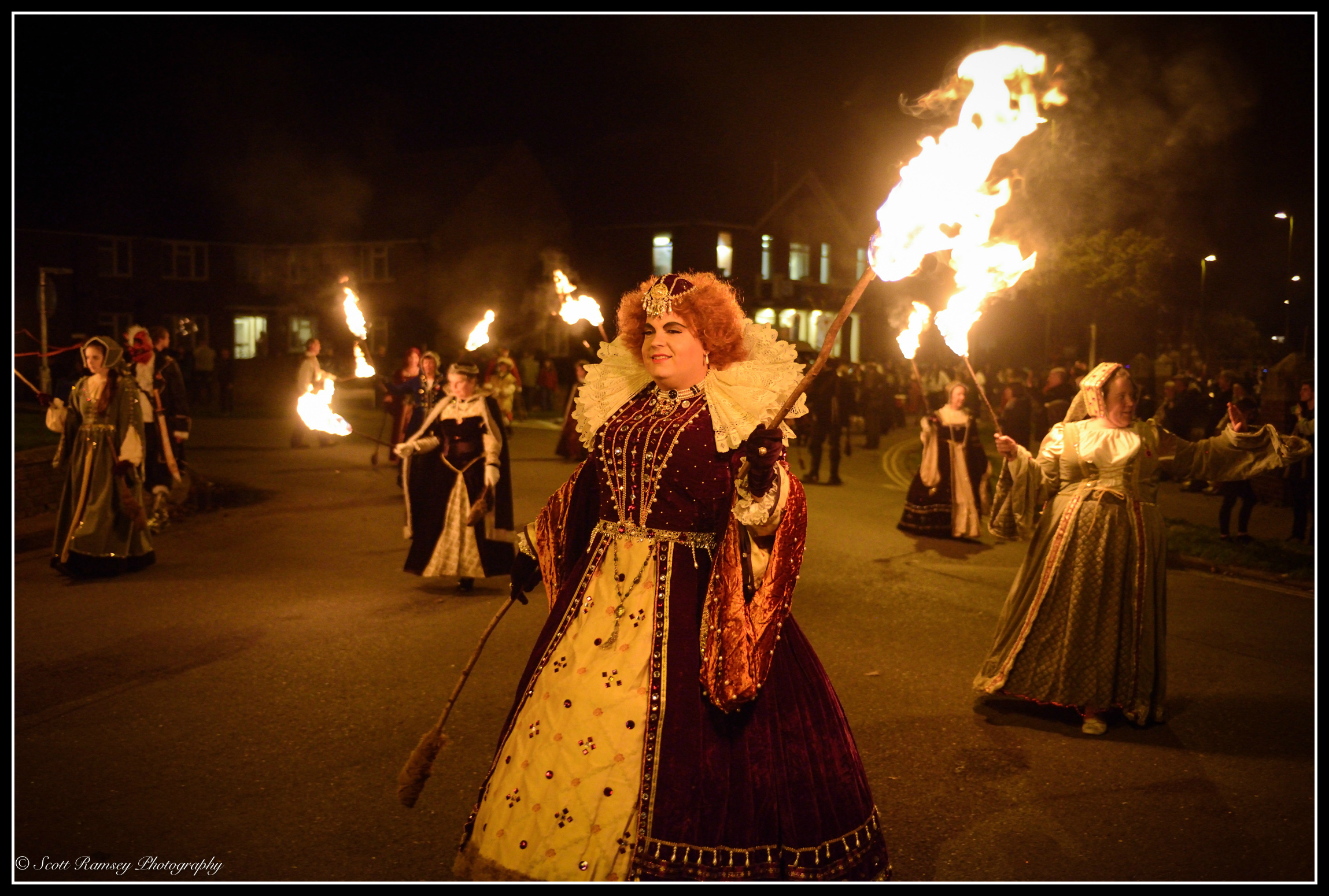 A member of the Littlehampton Bonfire Society dressed in a Tudor costume holds a flaming torch as she walks through the Littlehampton streets.