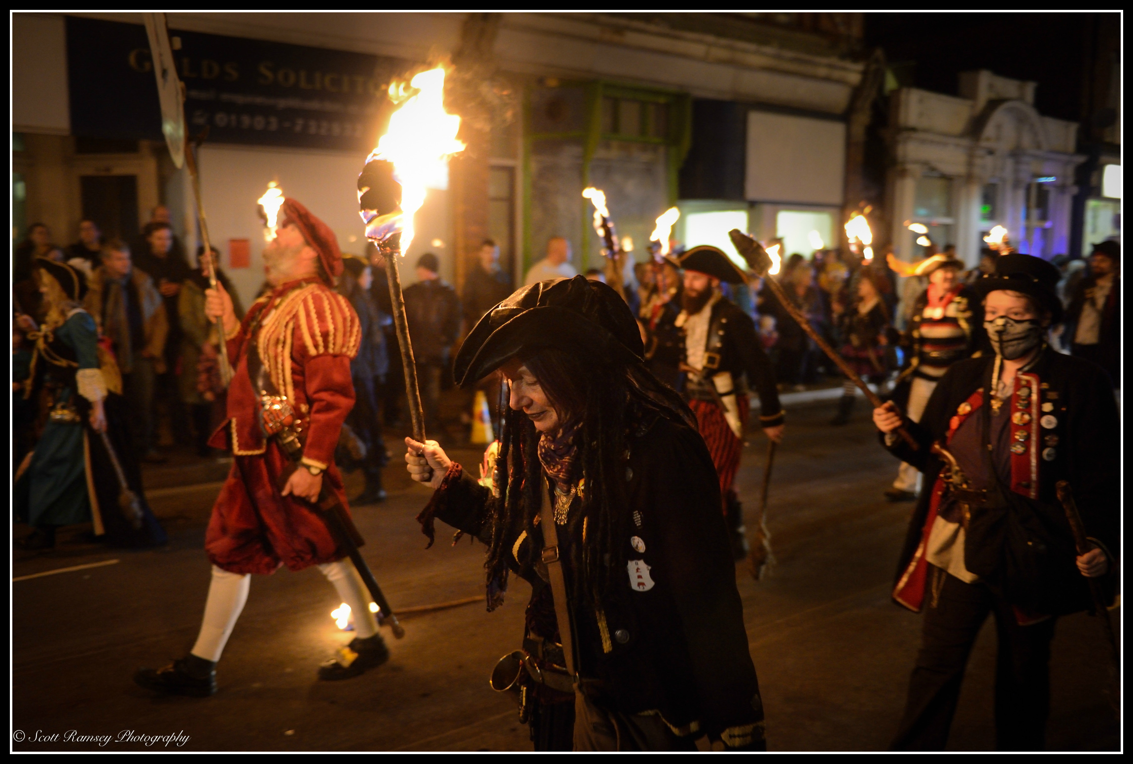 A member of the Eastbourne Bonfire Society dressed as a pirate holds a flaming torch as she walks through Littlehampton during the procession.