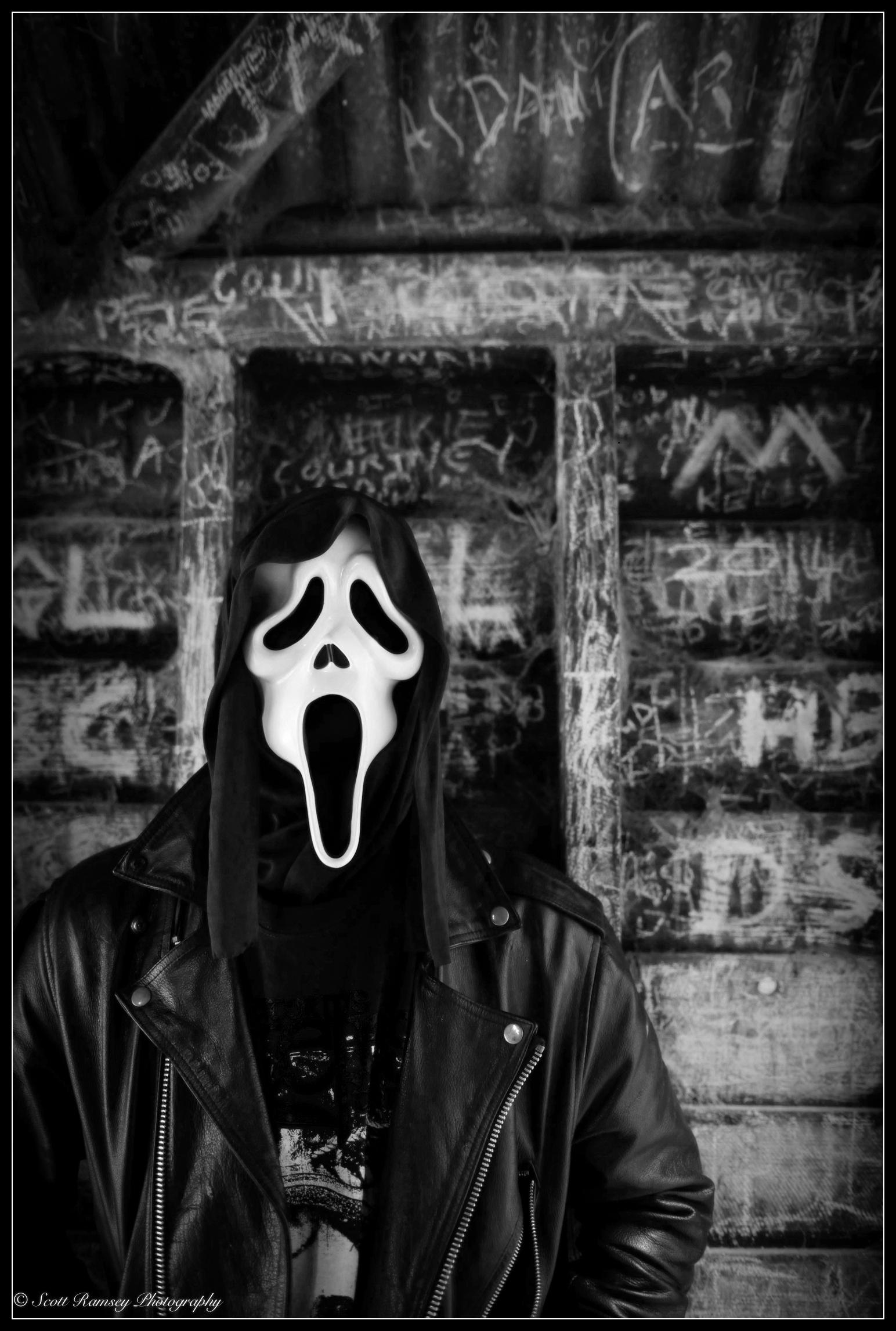 Halloween 2014. A masked man stands next to a graffiti filled wall. © Scott Ramsey Photography