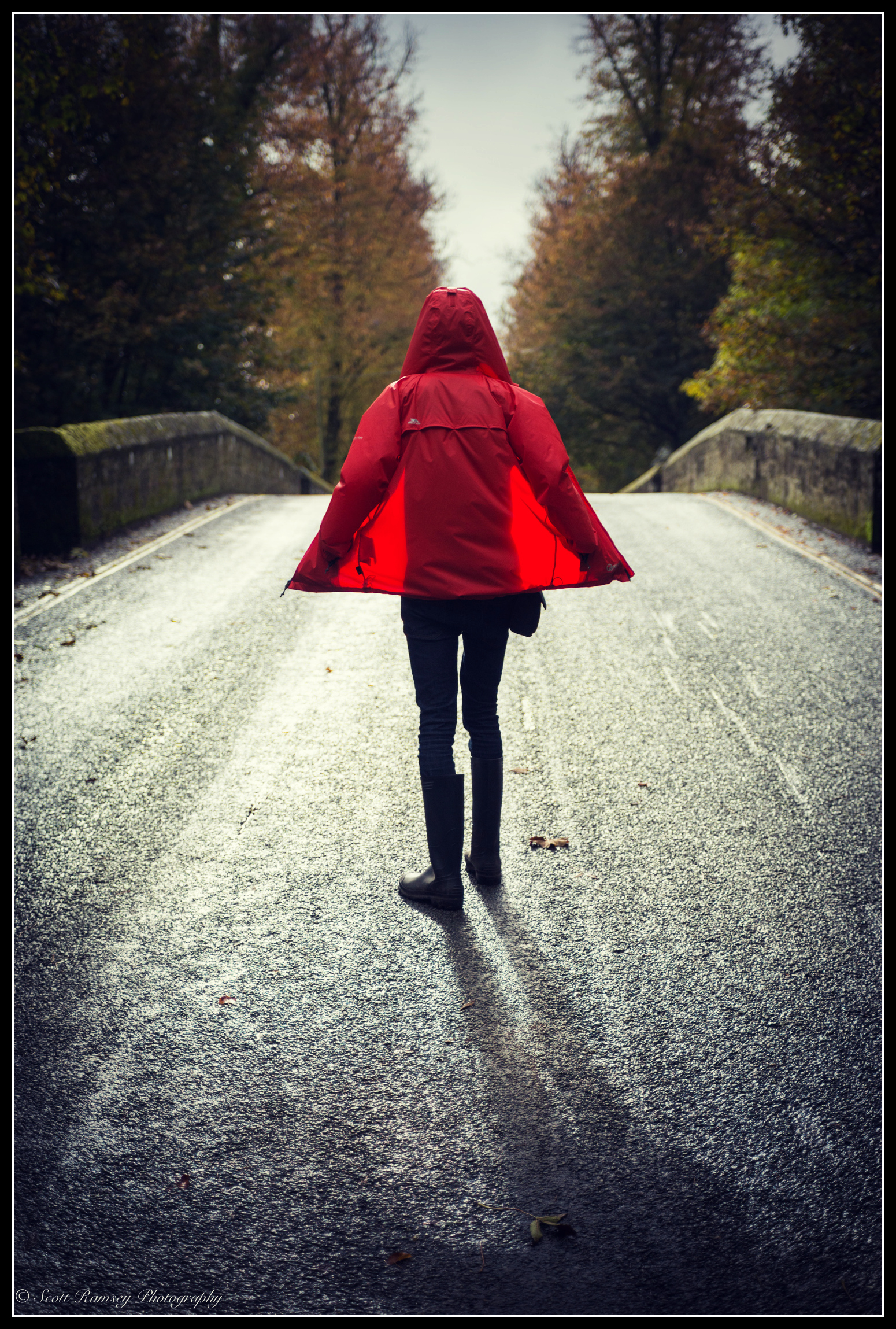 A brief gap in the rain clouds allowed the beautiful autumn light to shine through highlighting the wet road and emphasising the colour of the red coat in this photograph that I took in Arundel, West Sussex © Scott Ramsey Photography