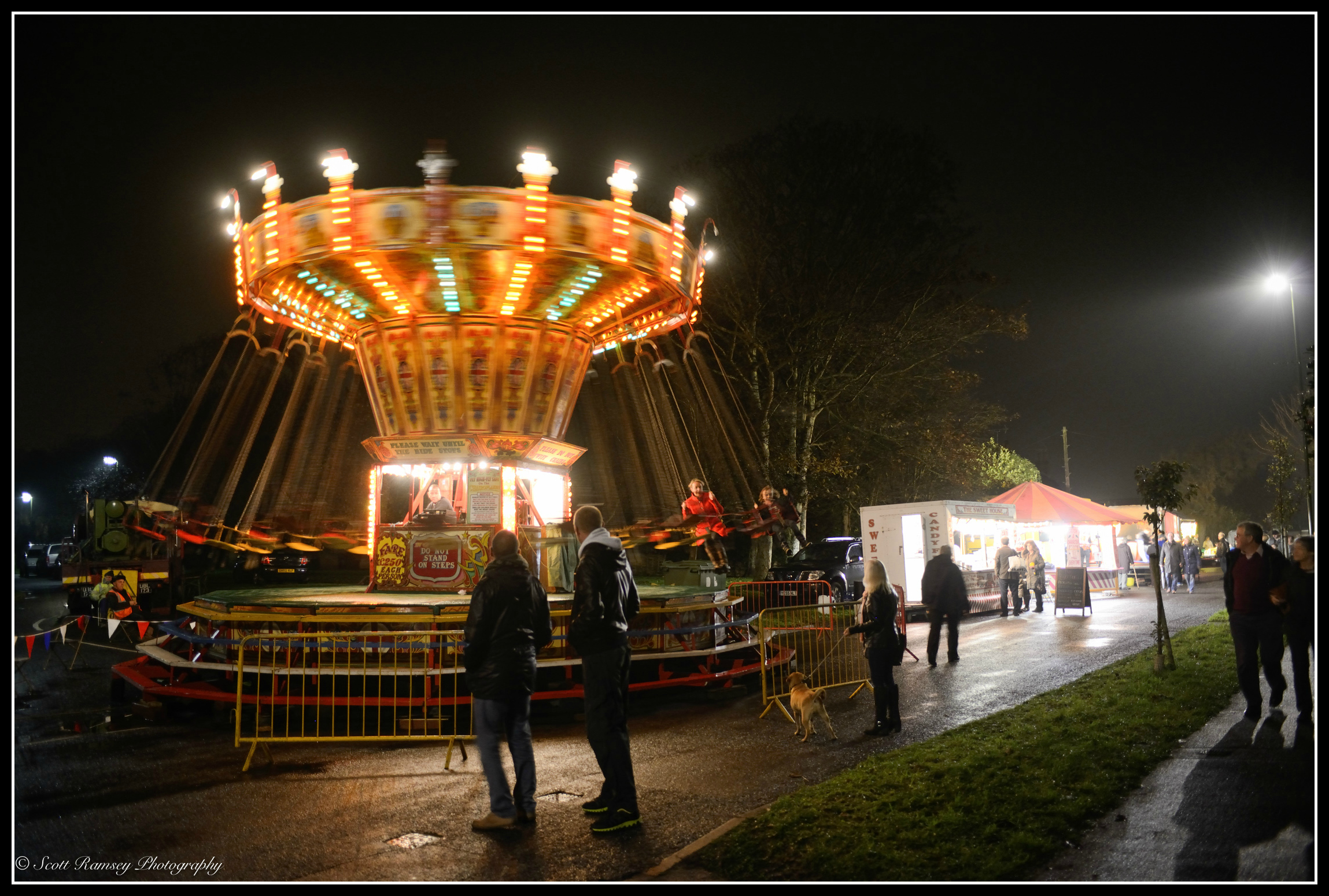 Lights are blurred as a traditional fun fair ride spins at night during the Christmas Celebrations in East Preston, West Sussex.