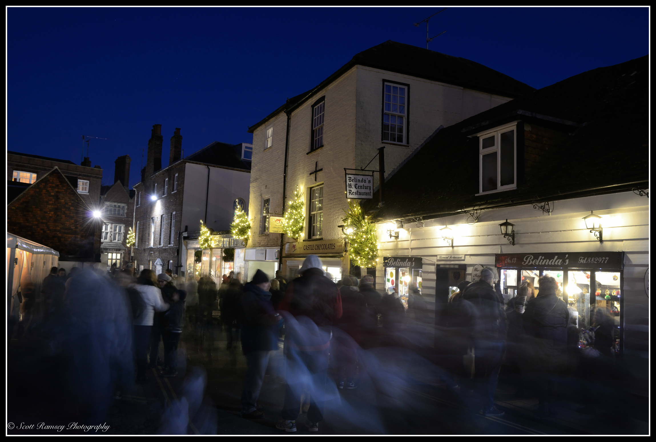People looked blurred as they walk past the camera in this photograph taken at night during the Arundel By Candlelight Christmas event.