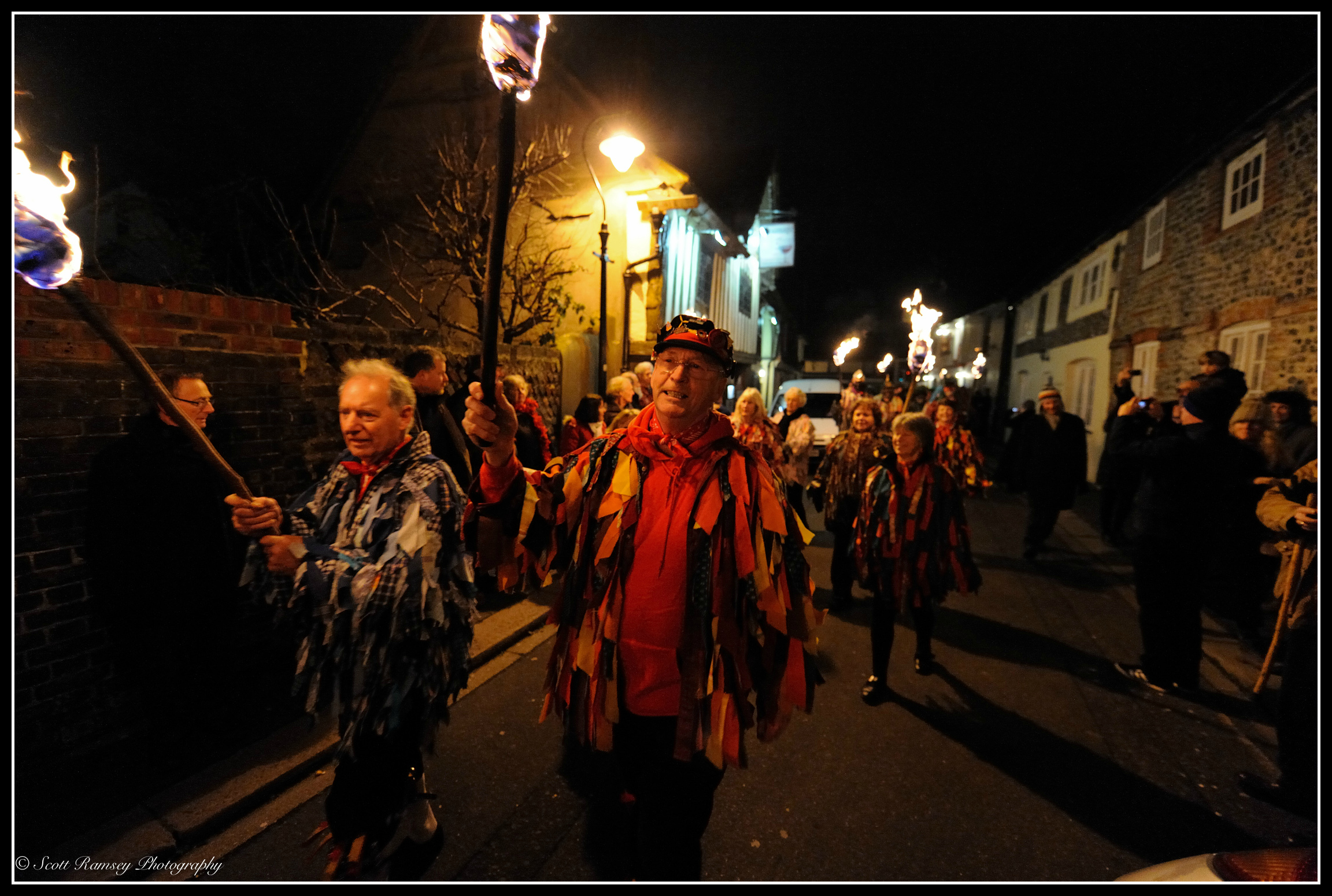 The Wassail at Tarring village. Members of the Sompting Village Morris carry  flaming torches as they lead the procession along the High Street in Tarring, West Sussex.