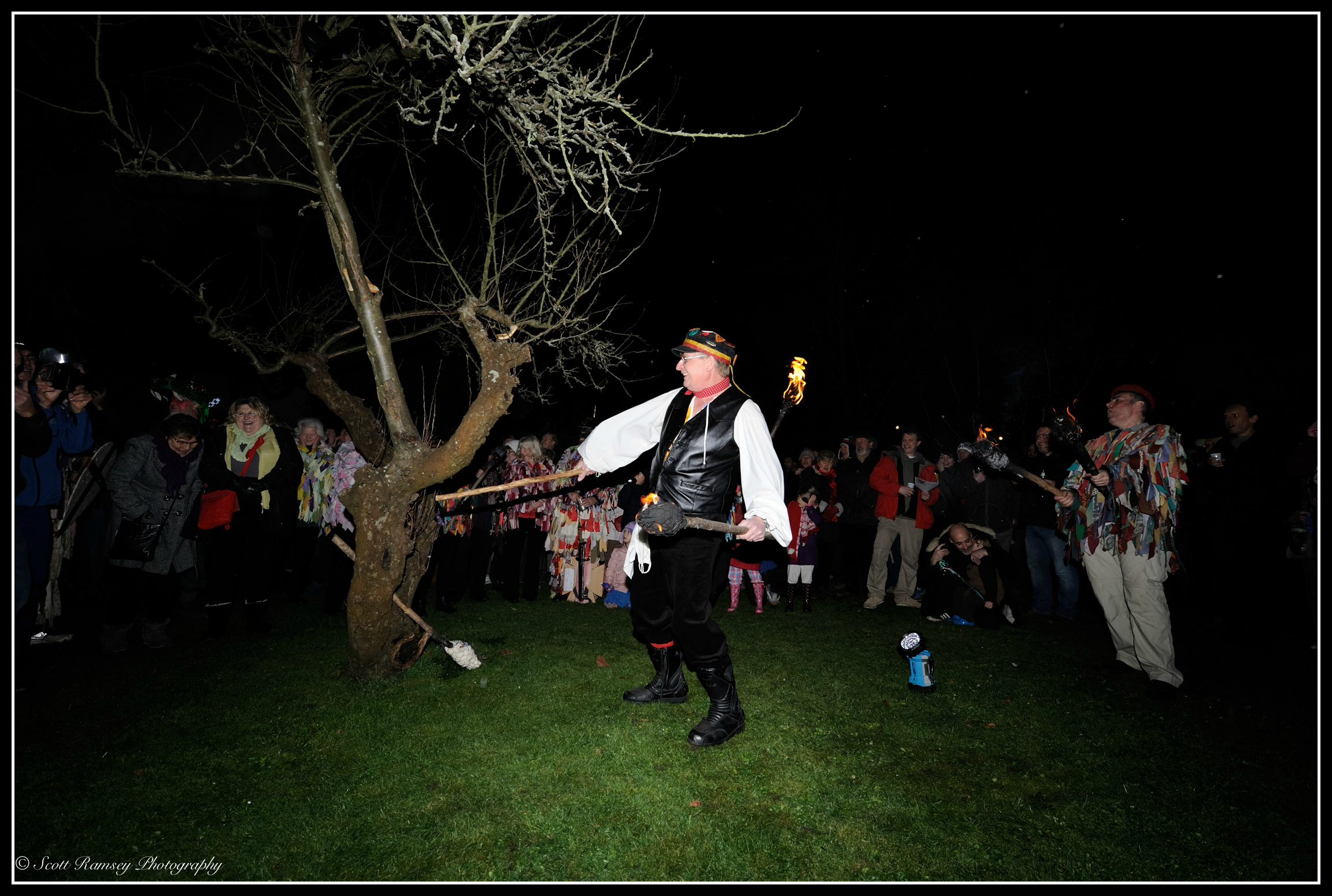To awaken the tree spirits a large stick is hit against an apple tree during the Wassail at Tarring village in West Sussex.