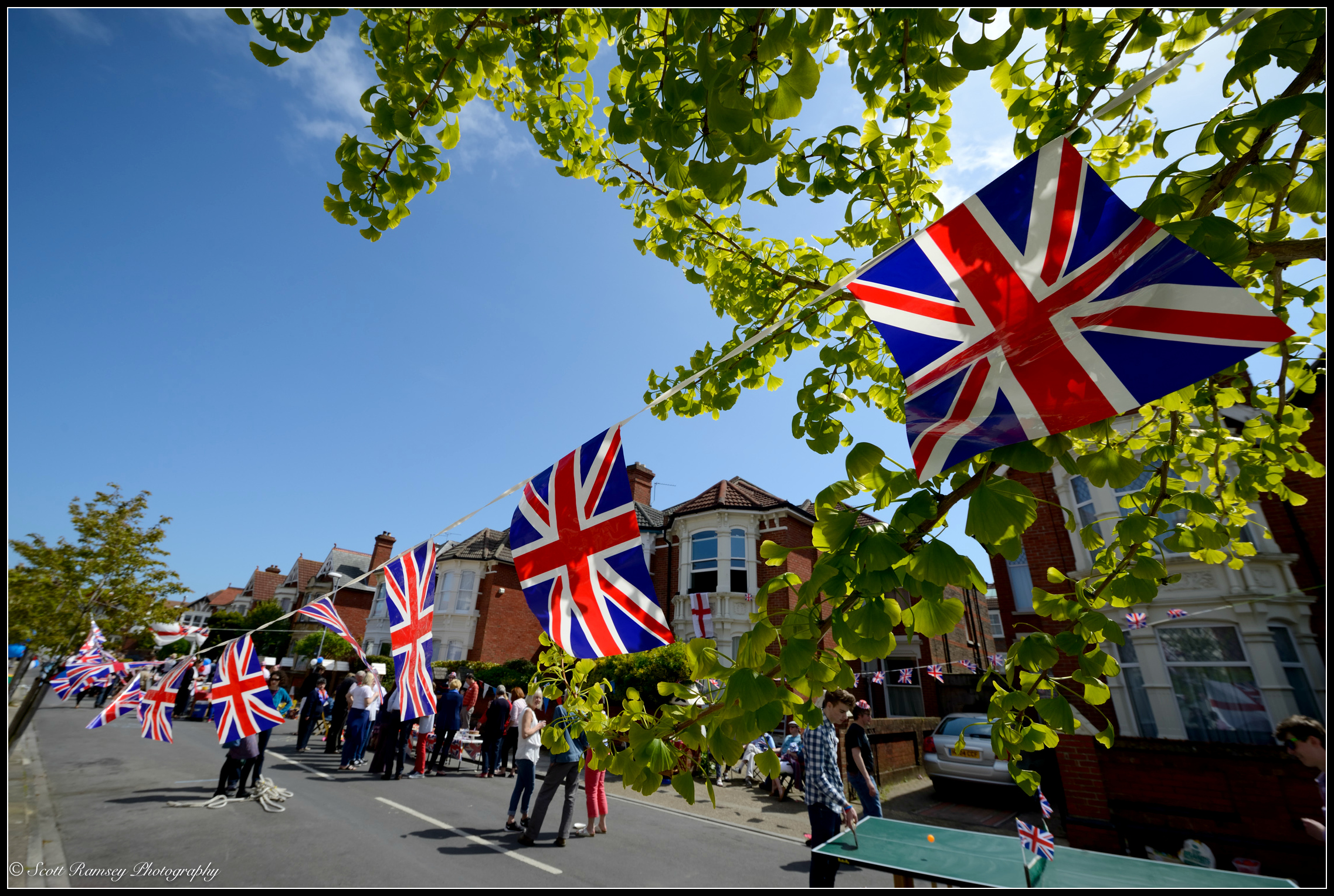 Flags hang from a tree during astreet party to mark theVE Day 70th anniversary in Southsea, Portsmouth, Hampshire, UK. © Scott Ramsey Photography.