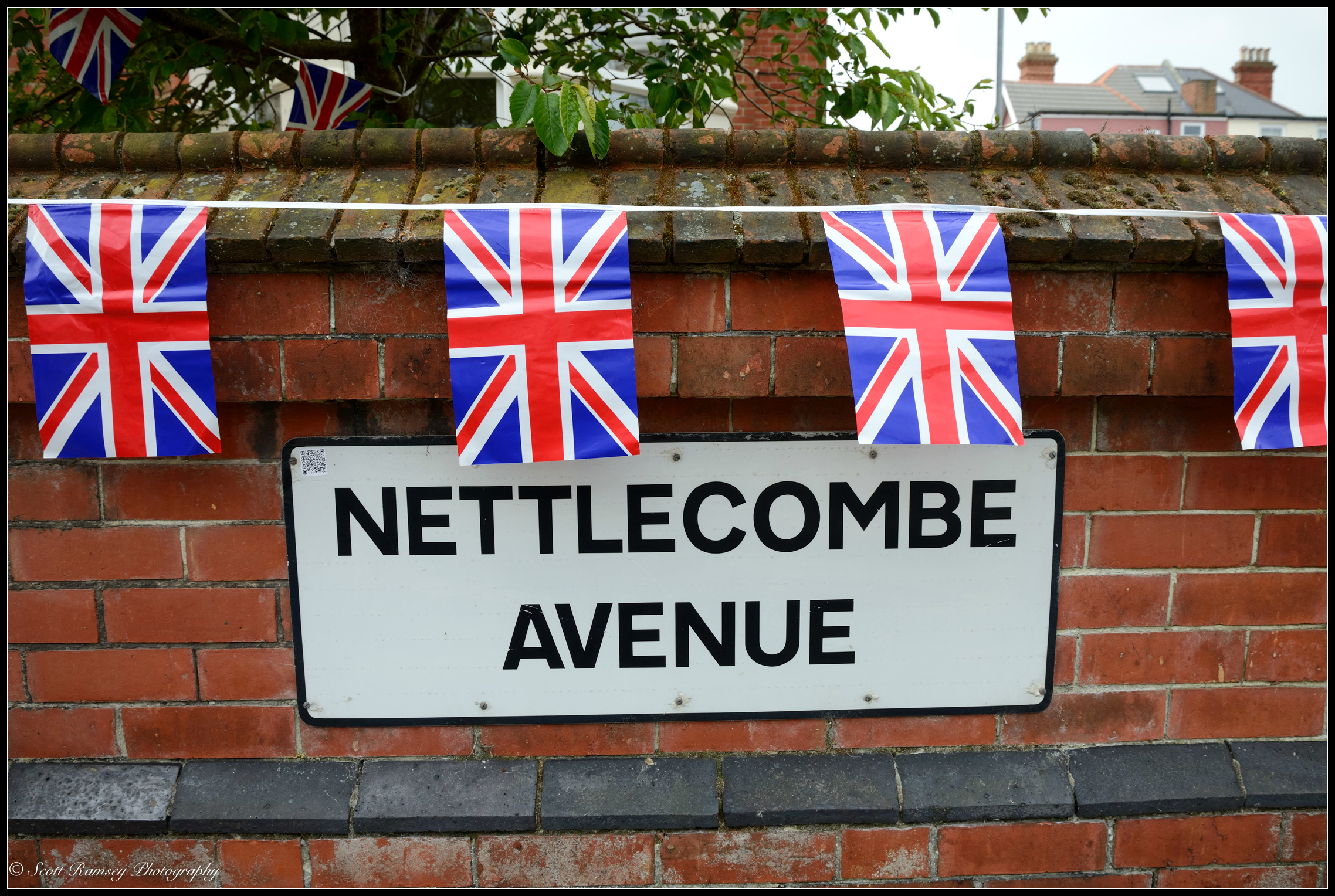 Unionjack flags hang from a garden wall andabove the Nettlecombe Avenue road sign in Southsea, Portsmouth. © Scott Ramsey Photography.
